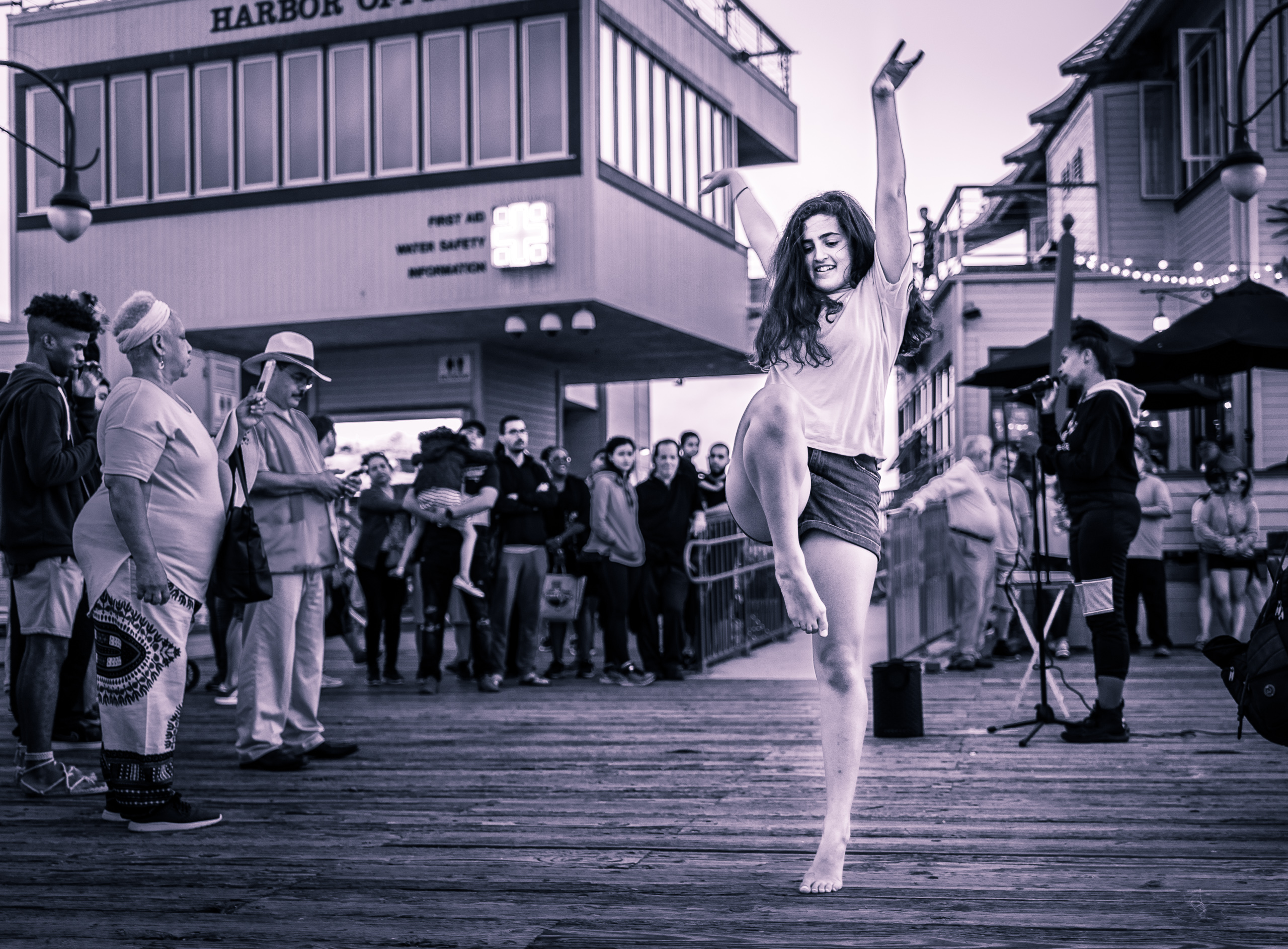 a young woman in denim shorts and bare feet gives an inspired dance performance near the end of the Santa Monica Pier