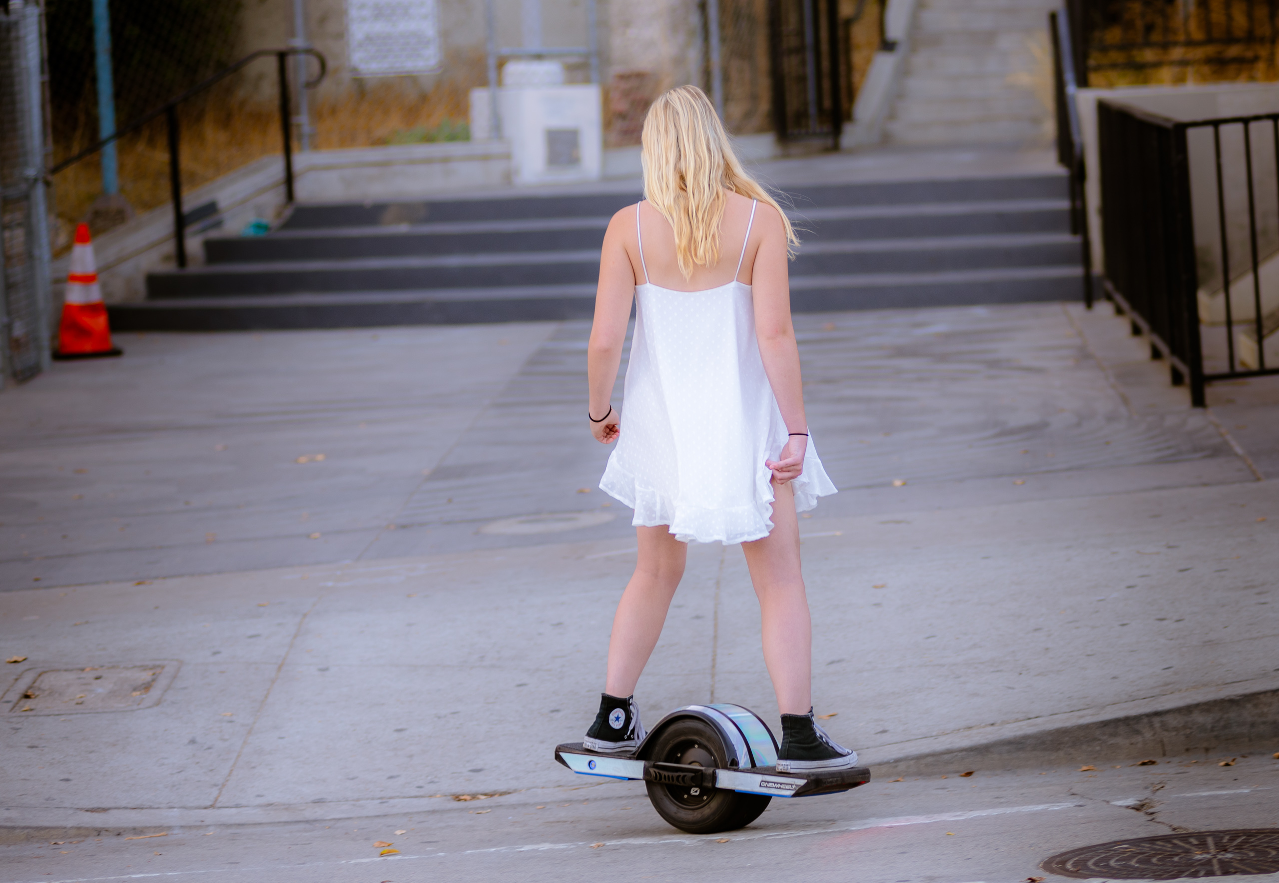 a girl in a flowy white dress rides a monowheel past Angel's Flight in Downtown Los Angeles
