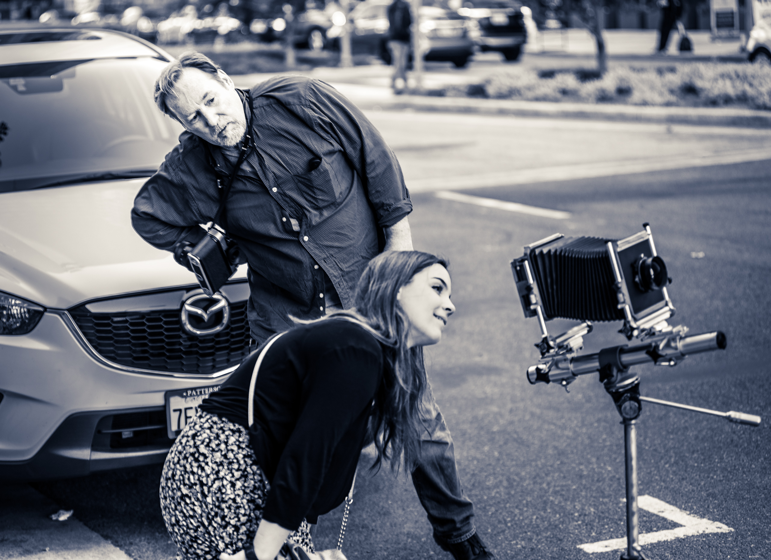 a man and a woman gaze into the back of a 4x5 view camera on a tripod on Grand Avenue in Downtown Los Angeles