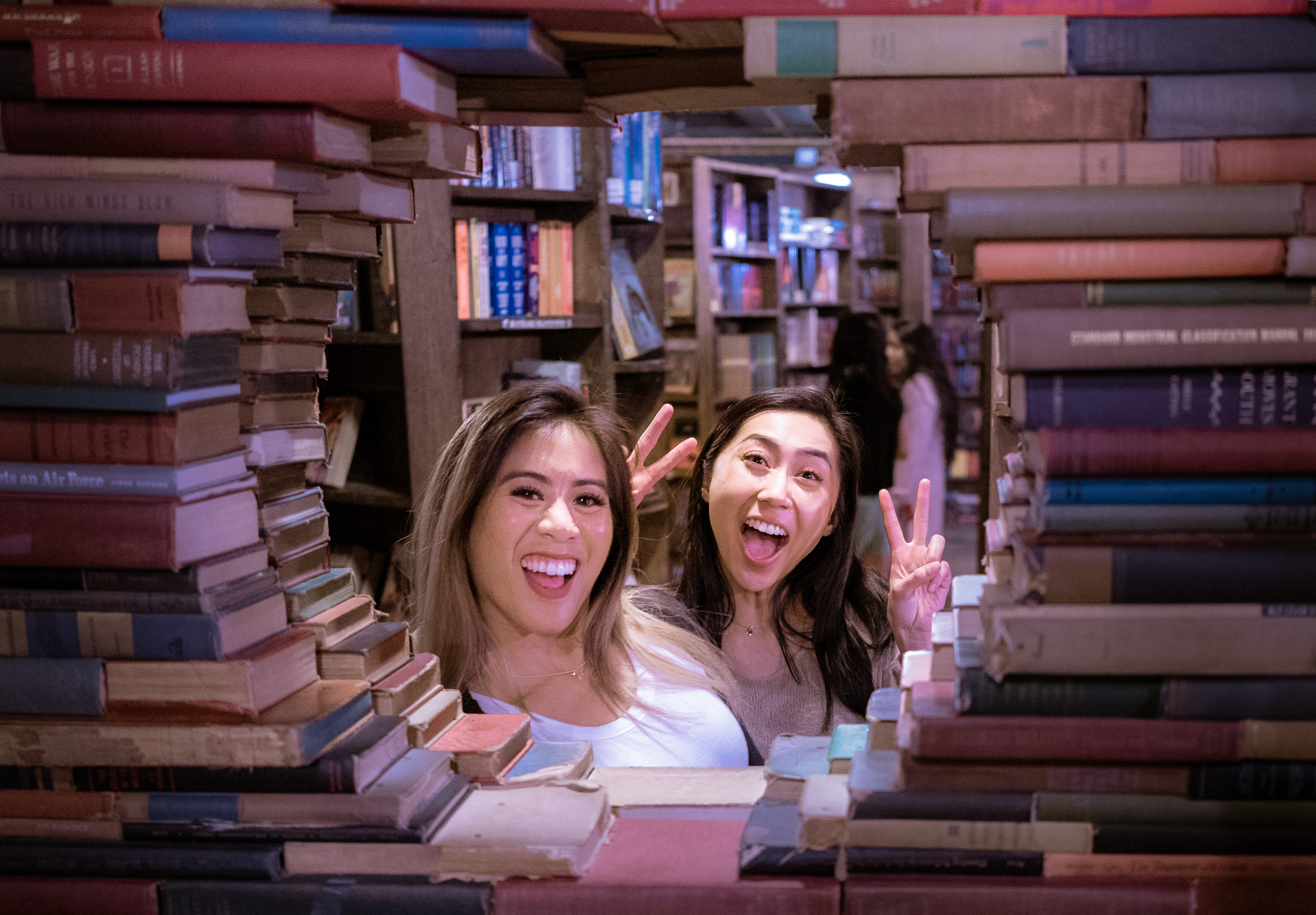 """Two women smile as they peer through """"The Book Loop"""" at The Last Bookstore, in Downtown Los Angeles"""