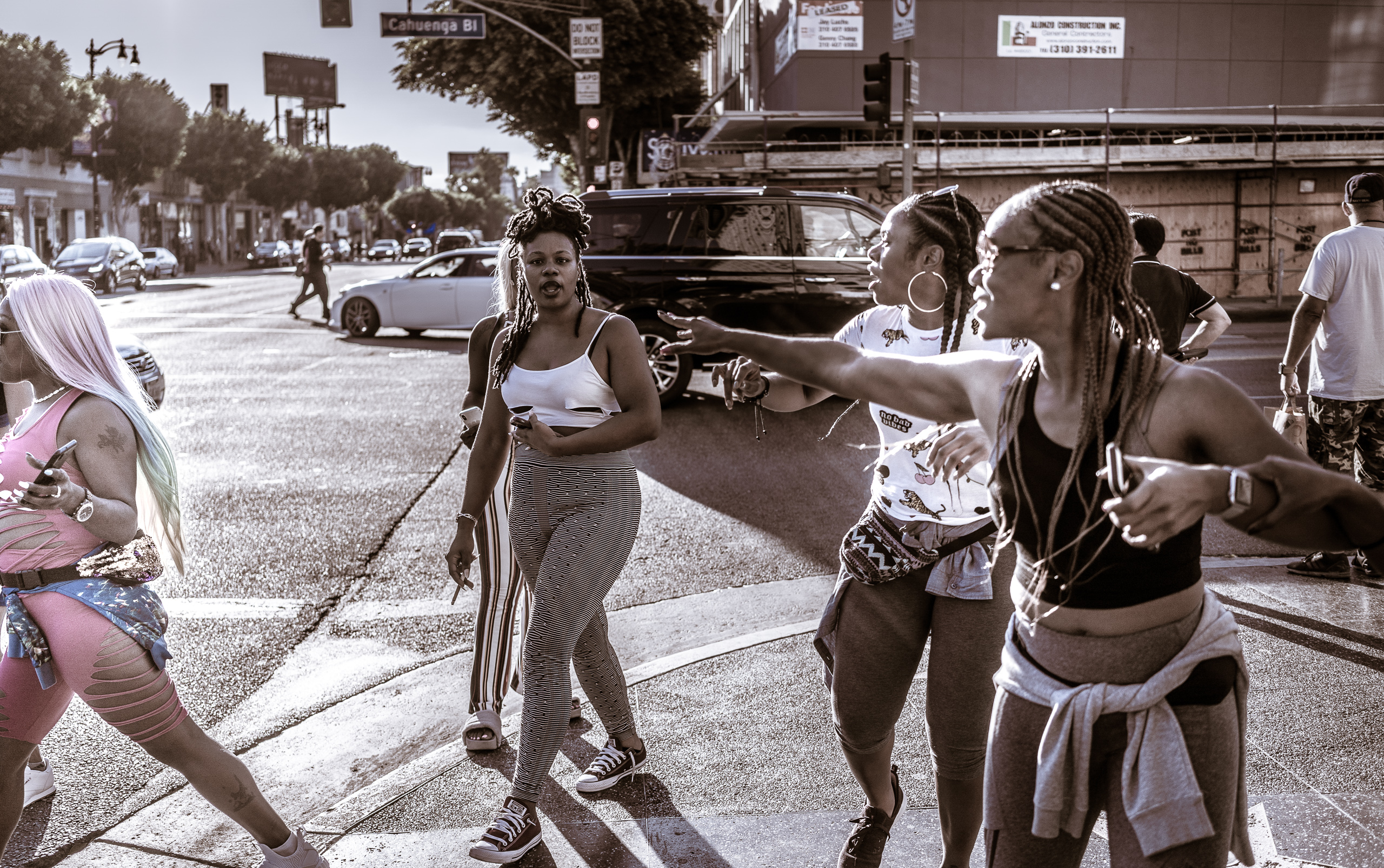 6 women on the corner of Hollywood & Cahuenga move in different directions. Two in the center face the camera as other move off as though a meetup has ended