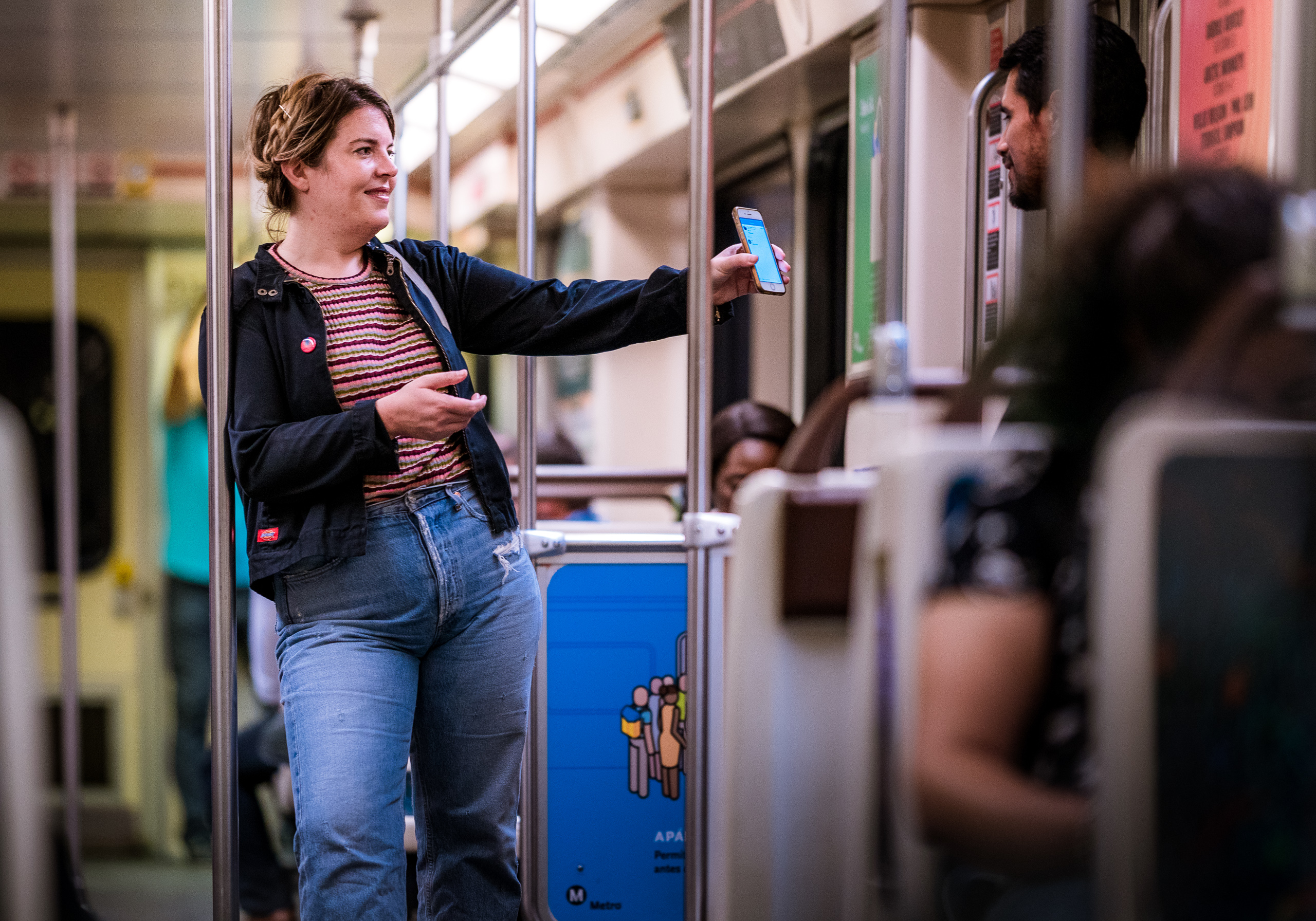 a woman in an LA Metro Red Line Car leans against a pole and extends her arm to show cell phone information to another commuter in the car