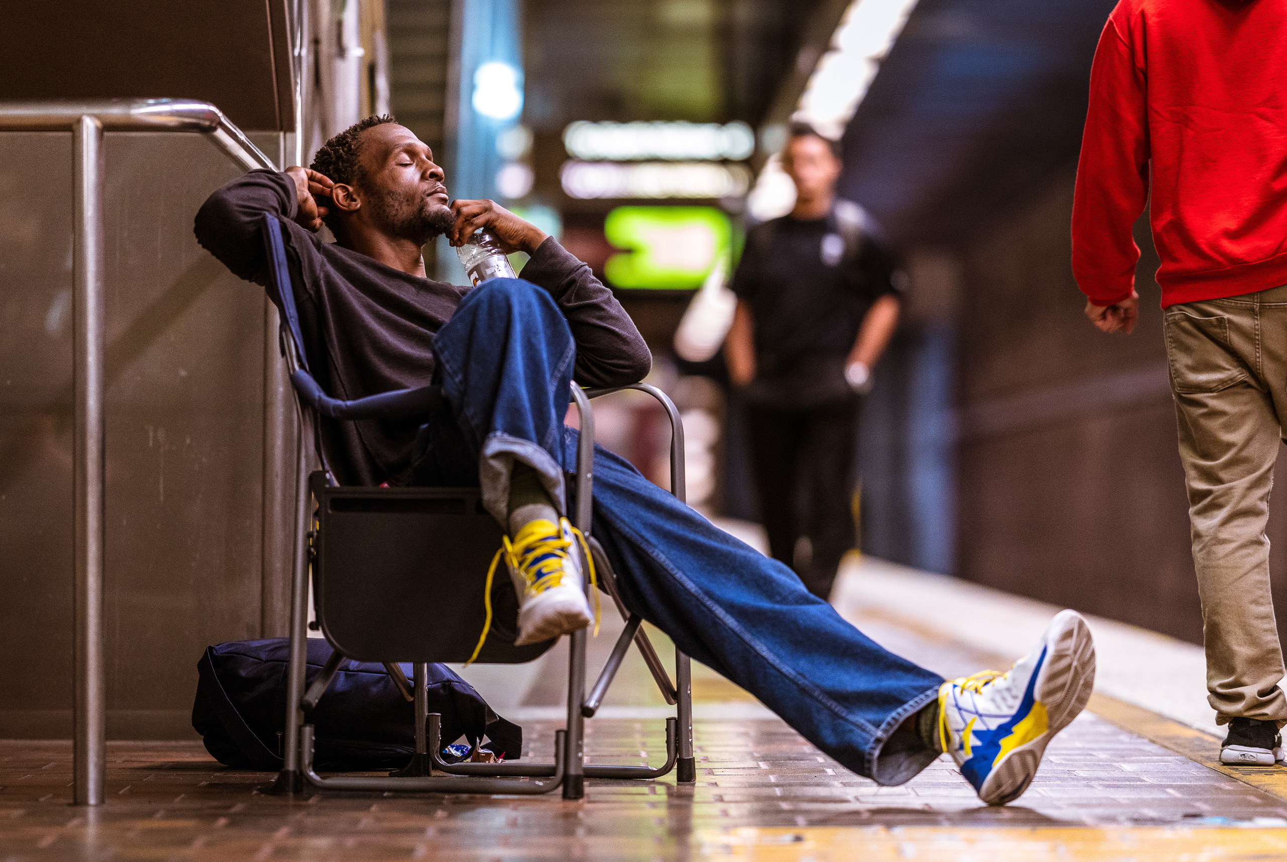 a man waiting at the LA Metro's 7th Street Metro Center (Julian Dixon) relaxes in a portable chair with one leg outstretched, the other curled over the side of the chair, and a bottle of Gatorade held near his head