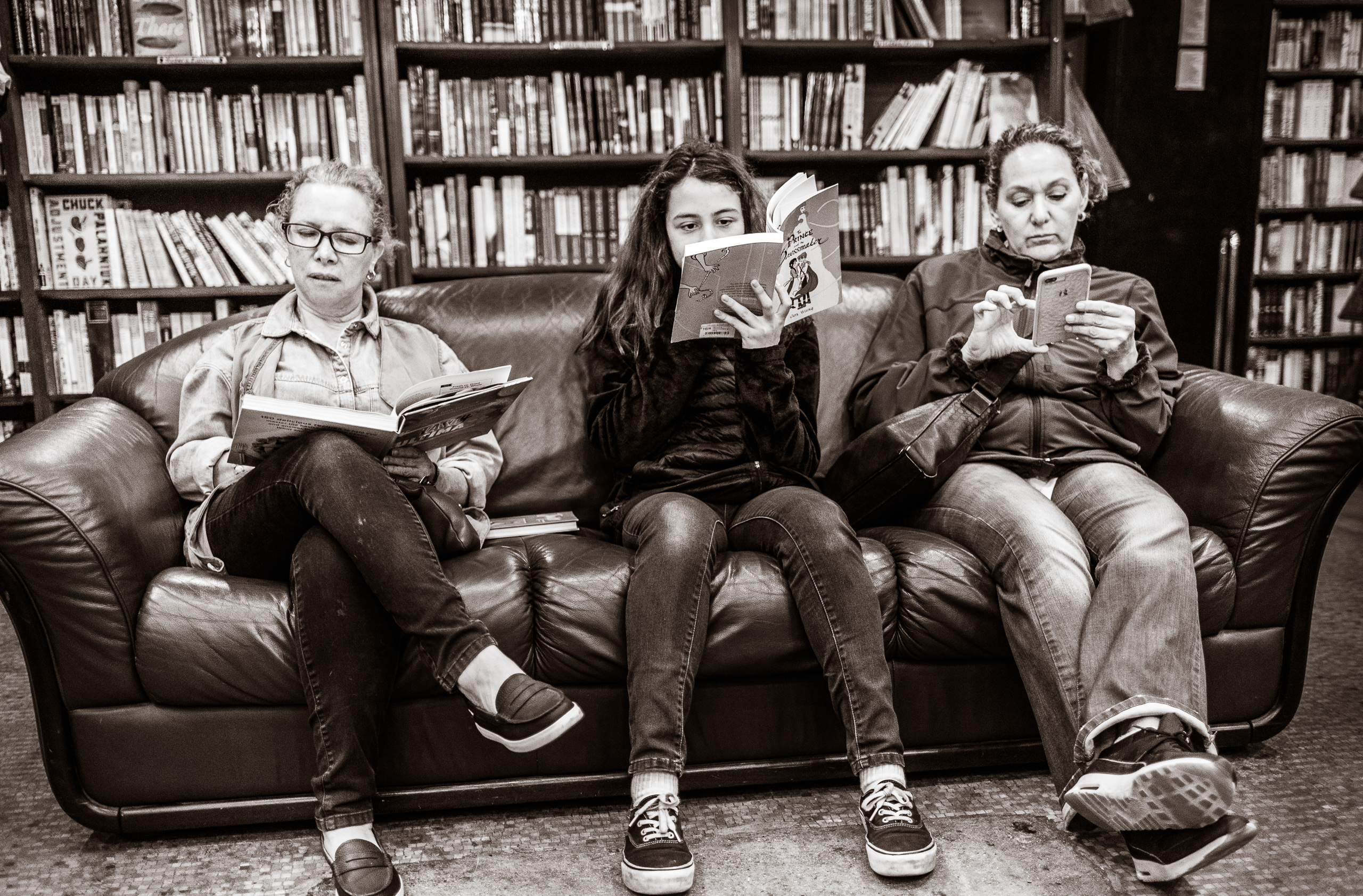 Two women and a girl sit on a couch inside The Last Bookstore in Downtown Los Angeles. The girl and one of the women are reading books. The other woman is doing something on her phone.