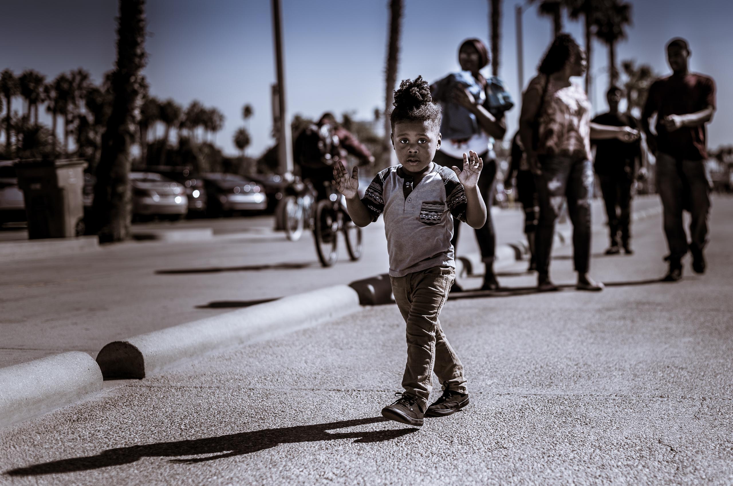 a young child walks along the pedestrian path between  Venice Beach and Santa Monica