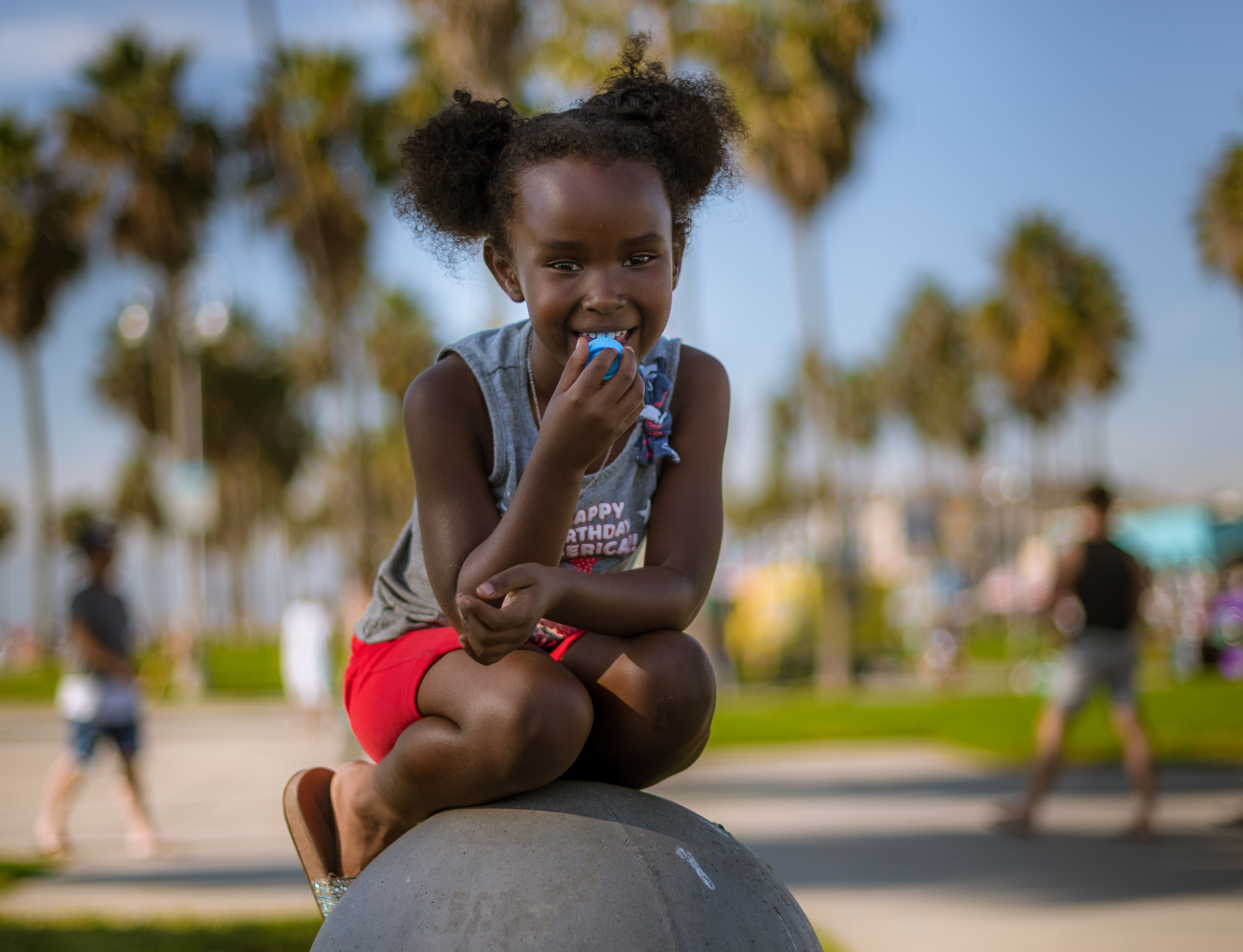 a young girl sits on top of a concrete bollard near the Venice Beach Basketball courts