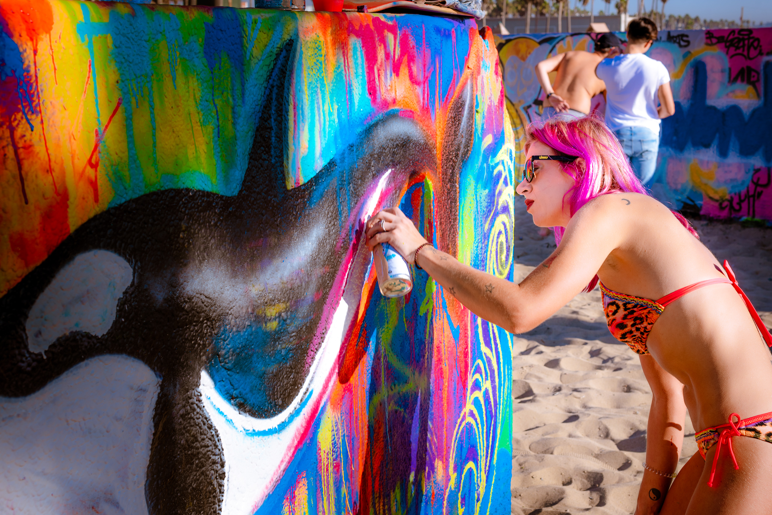 Lizzie Green, @6lizabeth3, painting a whale piece with a color field background at the Venice Beach Art Walls in Los Angeles, CA