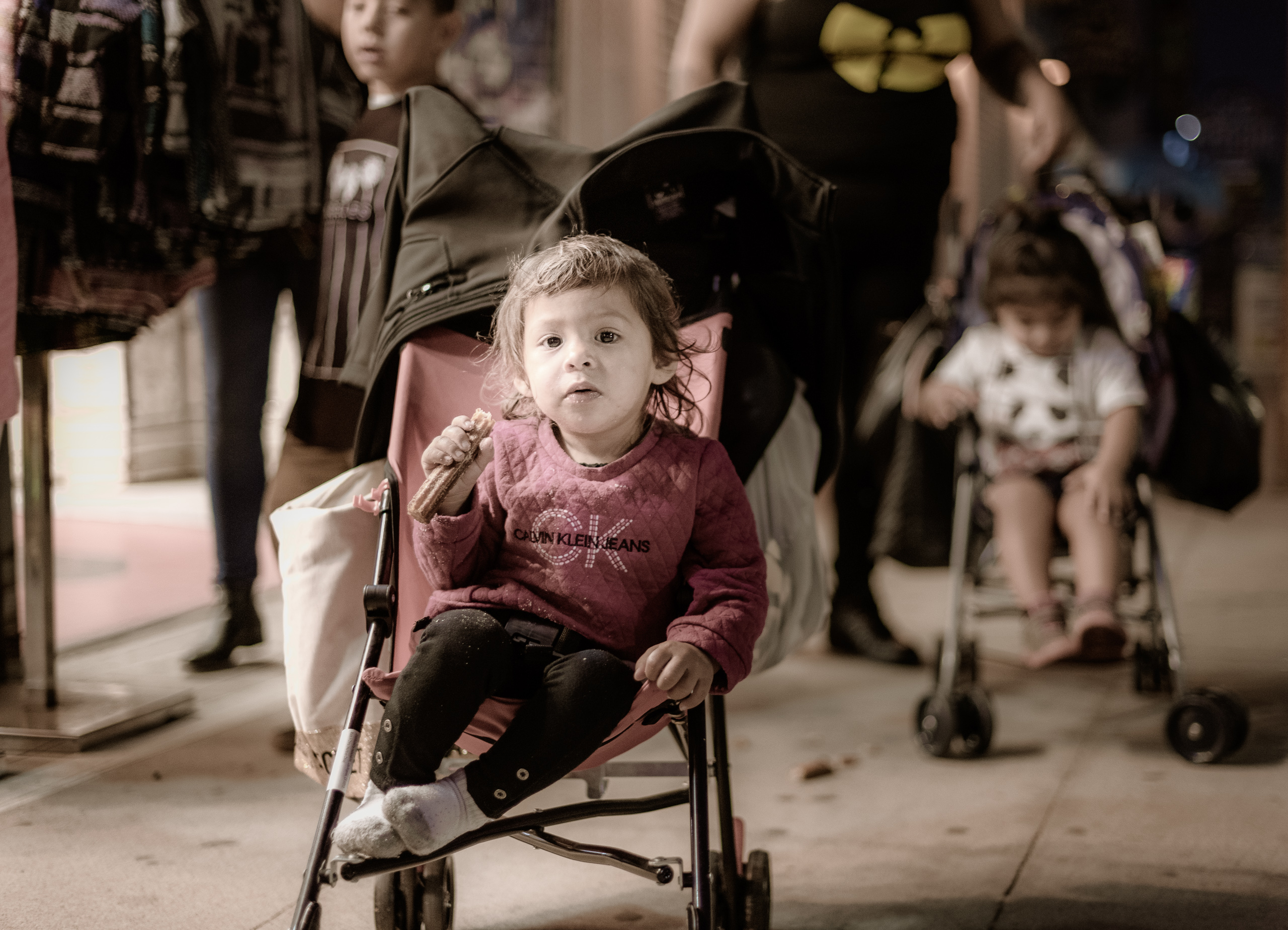 a young child in a stroller with his family behind him