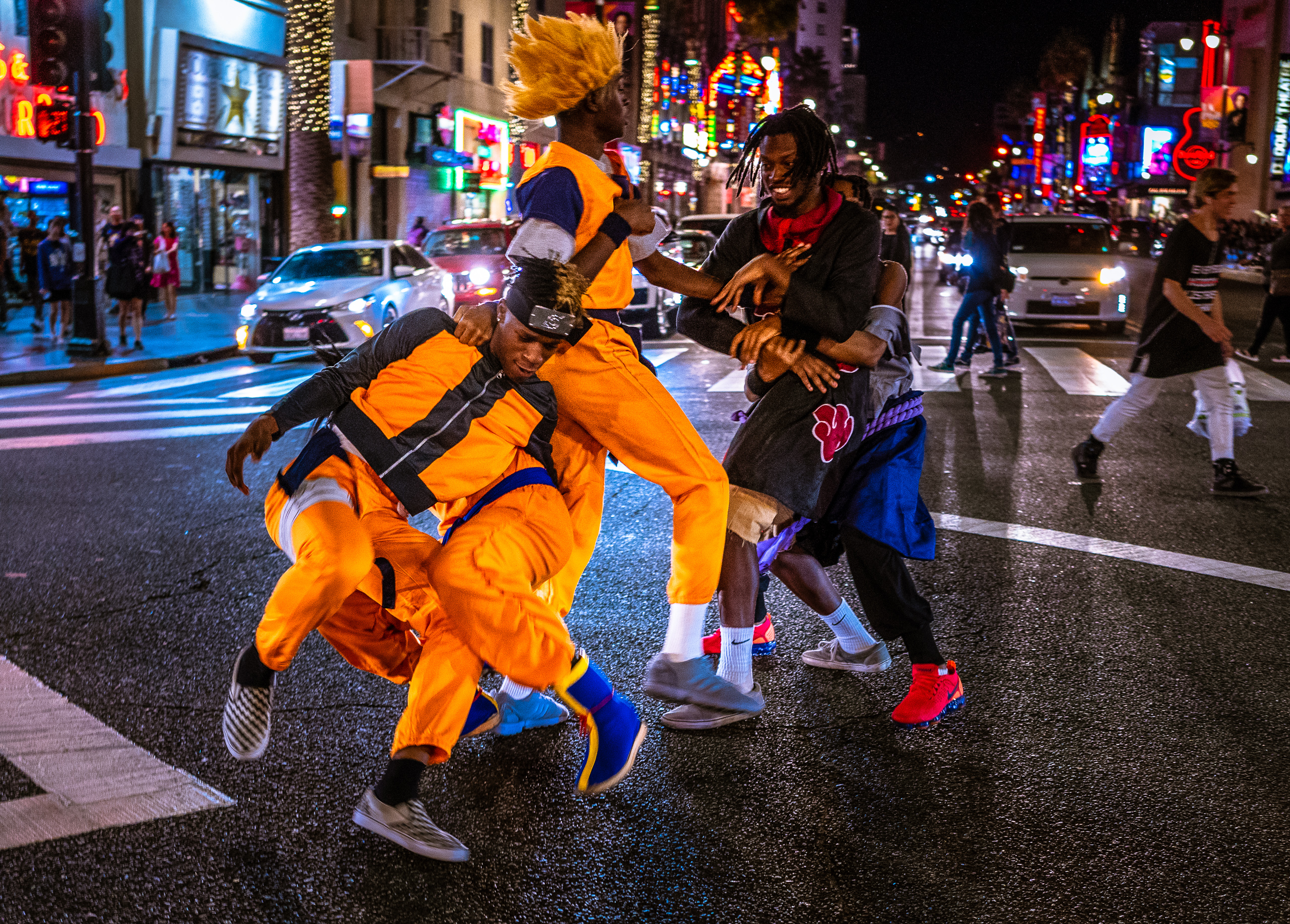 a half dozen men in bright orange costumes and huge hair wigs put on a mock fight or battle in the middle of the 4-way crossing at Hollywood & Highland in Hollywood, California