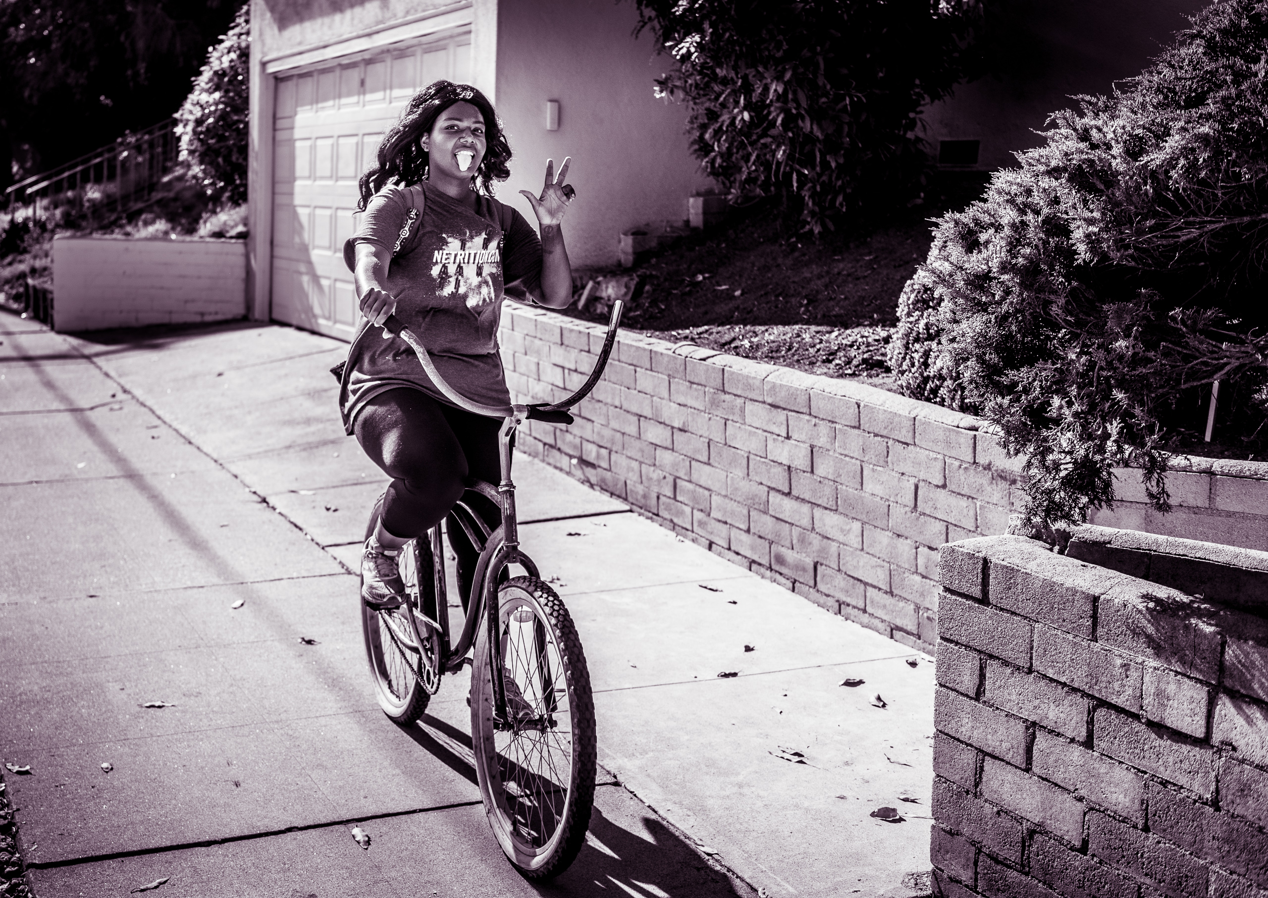 a woman rides a bike down the sidewalk of Olympic Blvd near Balsam Avenue in Century City, Los Angeles, California. As she passes me she sticks her tongue out and make a peace sign with one hand.