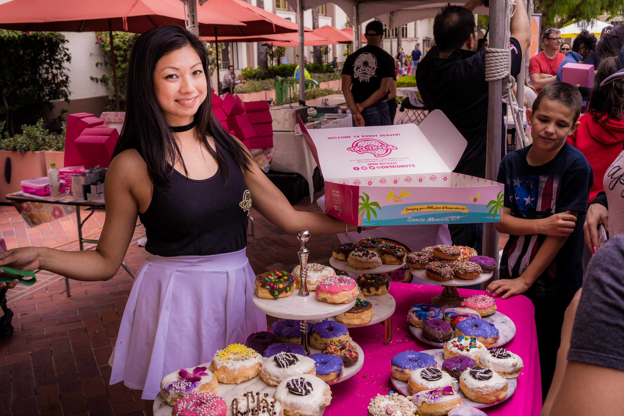 Mayly Tao, DK's Donuts heiress serves donuts from a table overflowing with many and varied brightly colored donuts at Union Station's  DTLA Donut Fest