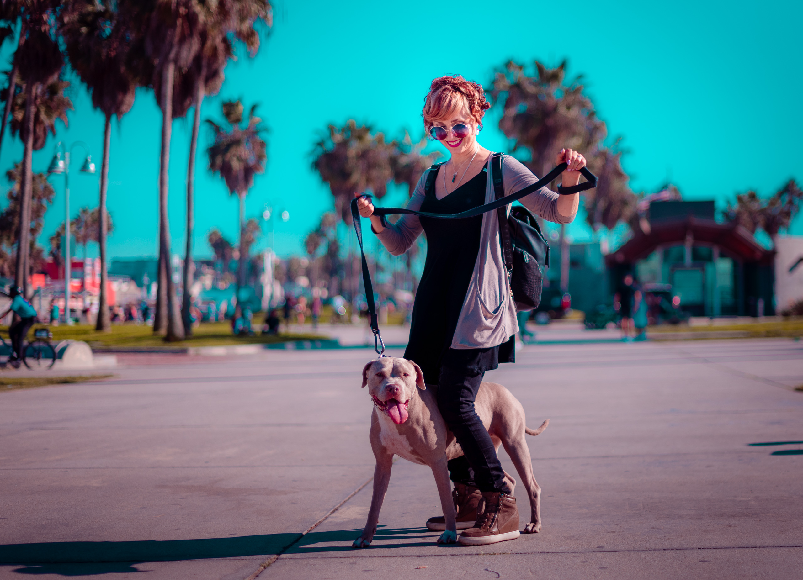 a woman with a big dog and a big leash tries to wrangle her dog on the Venice Beach boardwalk