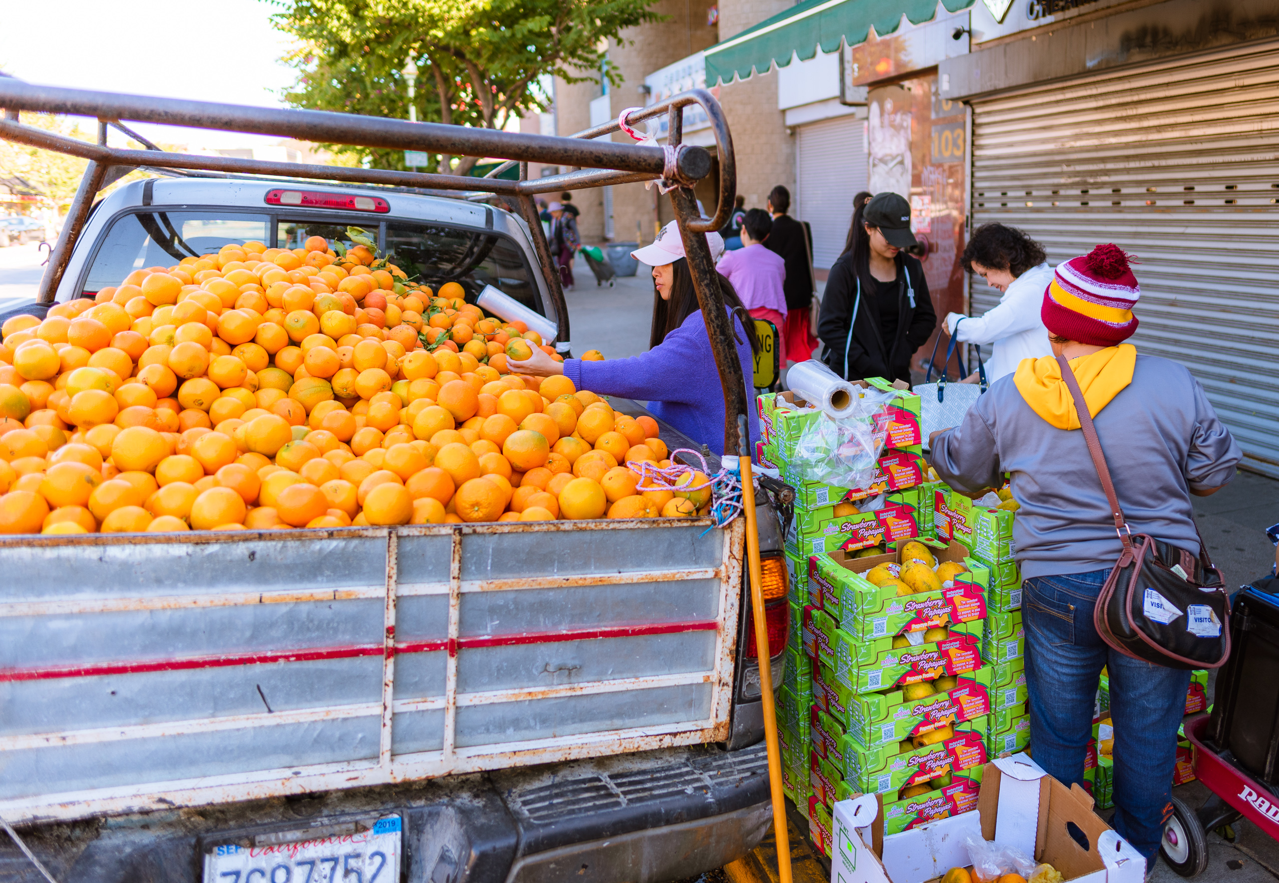 a pickup truck on the street in Chinatown. The back of the truck is overflowing with oranges.