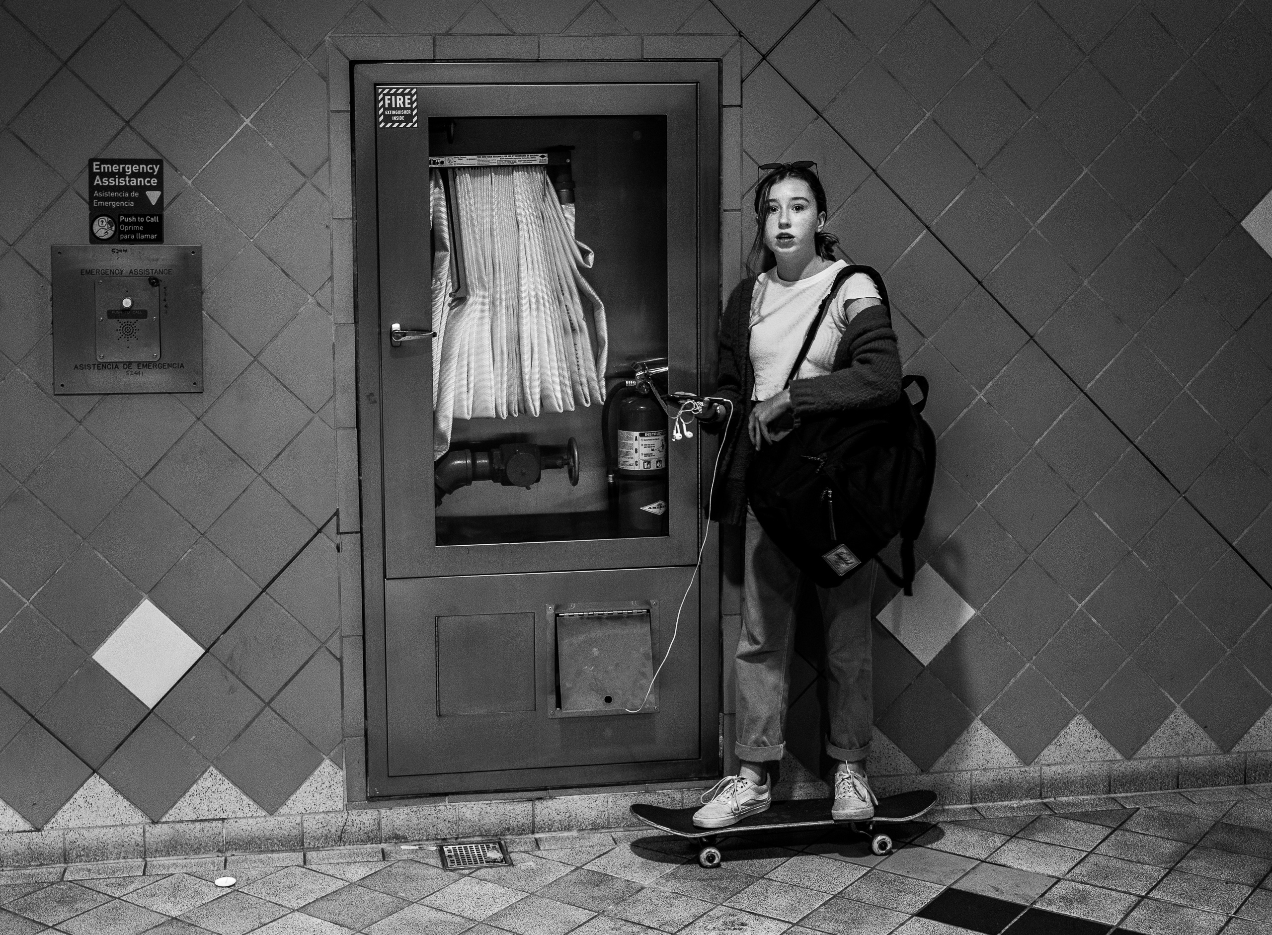 a young woman stands on her skateboard as she charges her phone from an electrical outlet in the exit stairwell from the LA Metro Red Line's Hollywood & Highland station