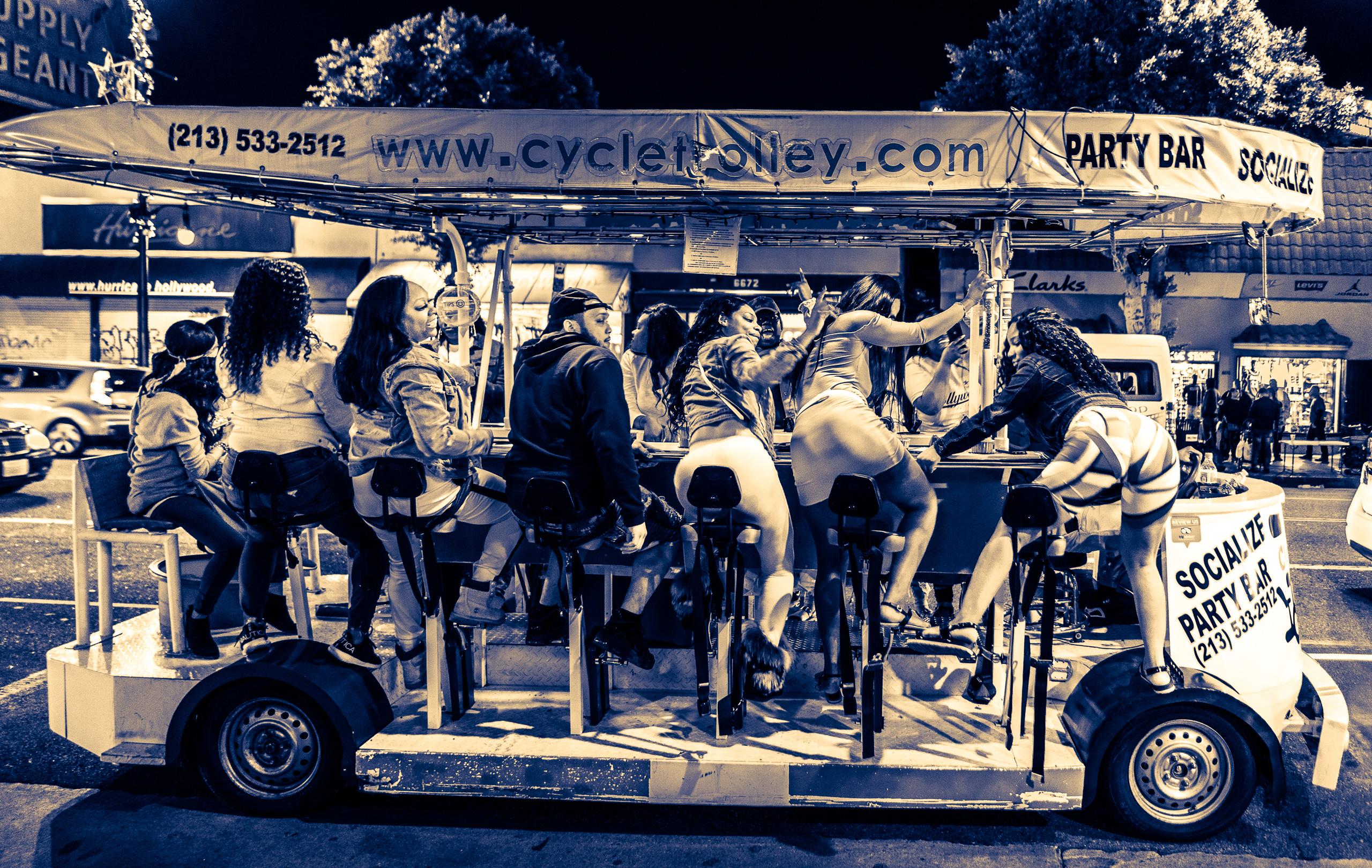 "A group of people ride the ""Cycletrolley"" down Hollywood Blvd. Several of the riders are twerking from their seats on the trolley."