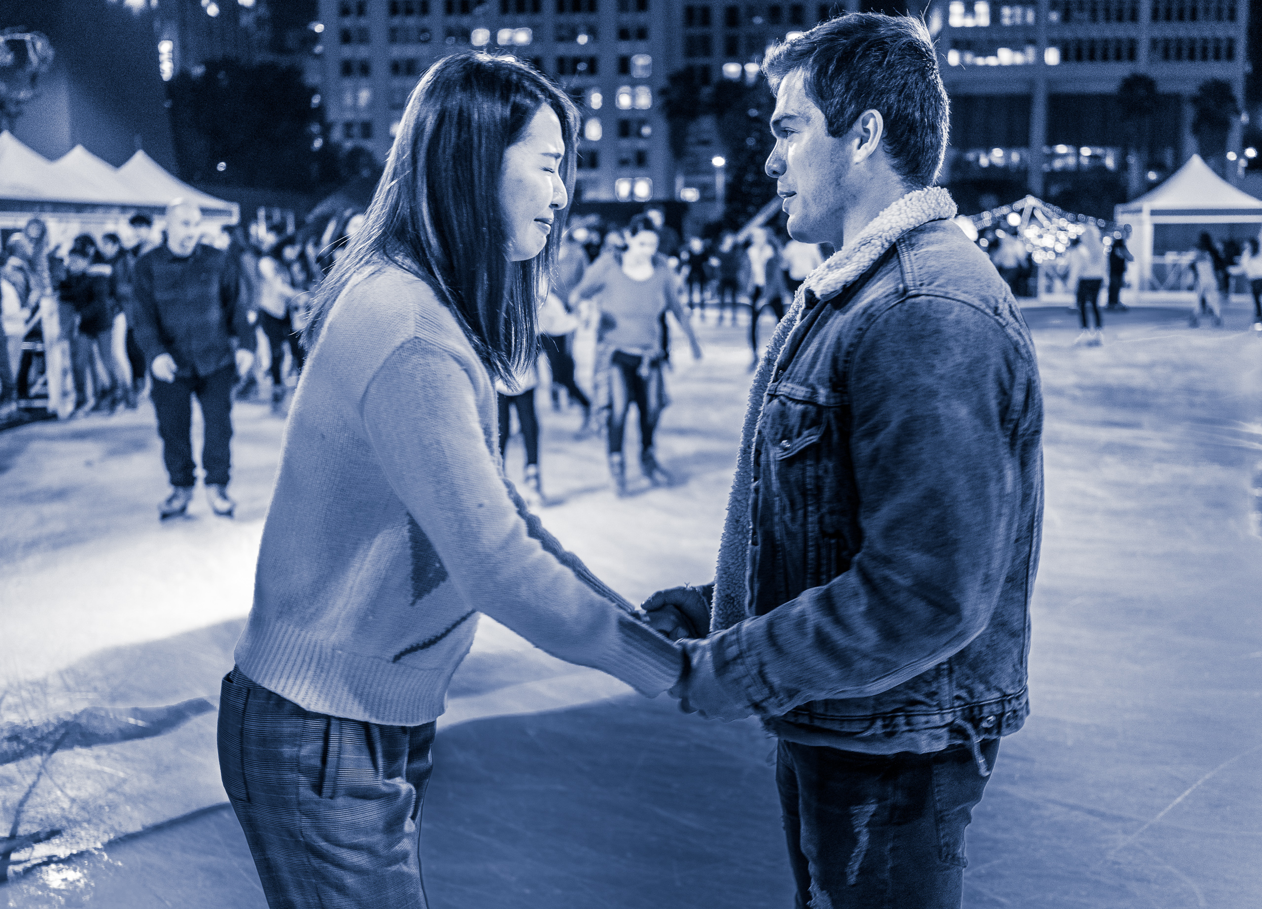 a couple on the ice at Pershing Square in Los Angeles. The guy is an experienced skater and is calm. The girl is a novice who is nervous and closes her eyes with a grimace