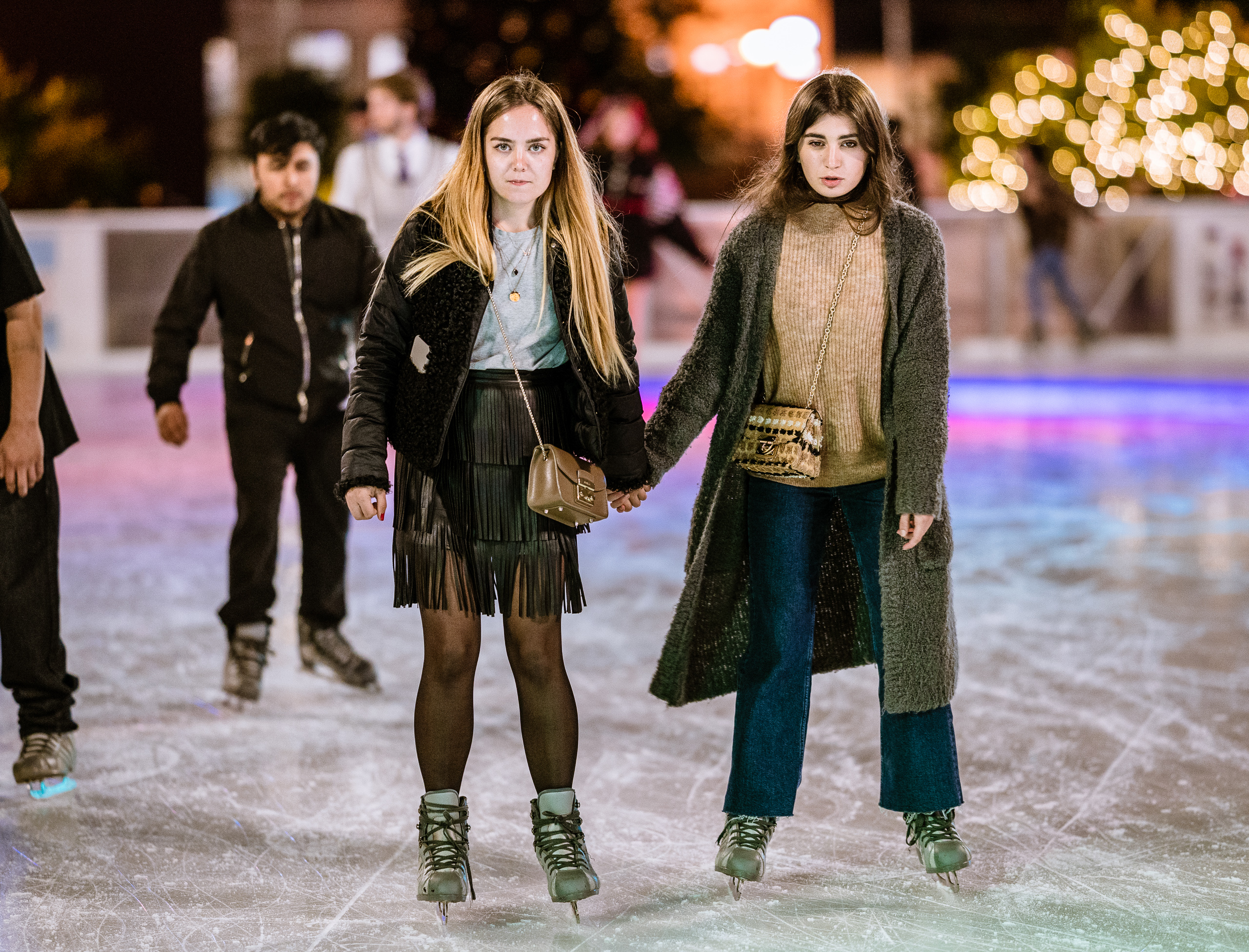 two women hold hands and skate along the ice at the Pershing Square Holiday Ice Rink in Downtown Los Angeles, Holiday Season 2018.