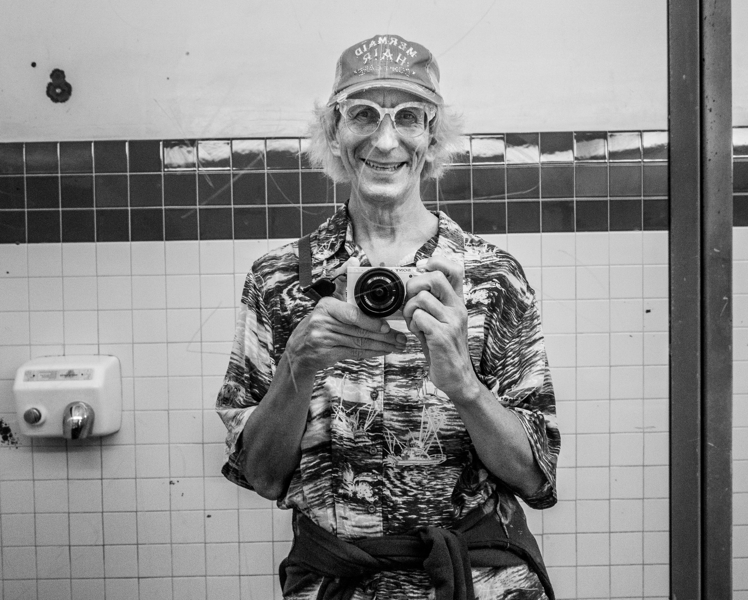 Glenn Zucman taking a selfie in the boy's room mirror at the Catalina Express terminal on Catalina Island, Los Angeles County, California