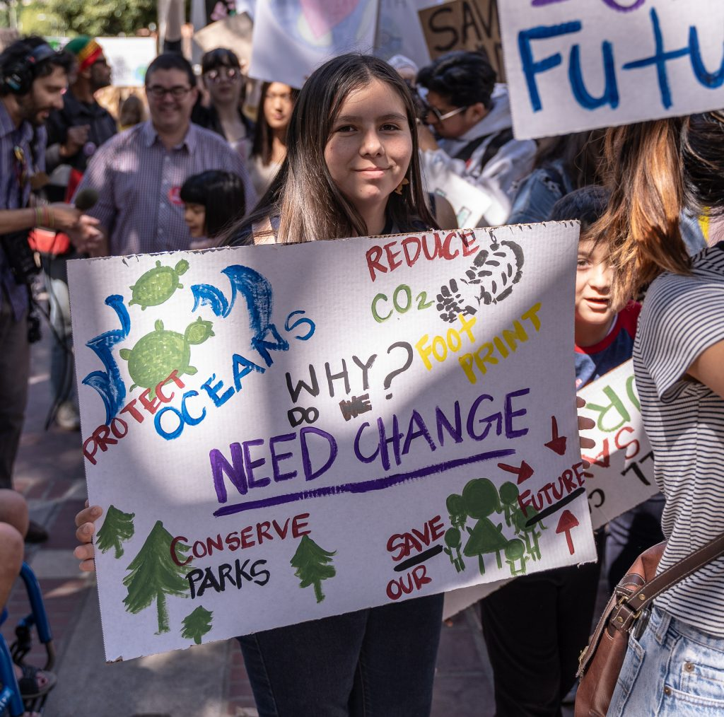 "Jessica Barrigo, 12, from Peters Elementary in Garden Grove carries her ""Why do we need change"" sign in the Youth Climate Strike at Los Angeles City Hall on Friday, March 15, 2019. Barrigo said she came to the march because ""I think we need to make a change"". ""Fridays for the Future"" is organized by 16-year-old Swede Greta Thunberg. The Los Angeles Youth Climate March is organized by 17-year-old Los Angeleño Arielle Martinez-Cohen. (Glenn Zucman/The Corsair)"