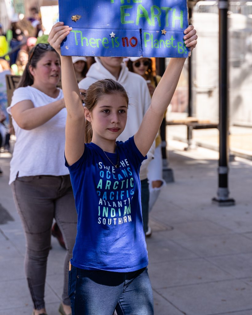 "Alyssa Rocca, 12, from South Pasadena Middle School marches in front of Los Angeles City Hall in the Youth Climate Strike on Friday, March 15, 2019. Rocca said she was marching because, ""I thought it was important to come here and support reducing climate change."" ""Fridays for the Future"" is organized by 16-year-old Swede Greta Thunberg. The Los Angeles Youth Climate March is organized by 17-year-old Los Angeleño Arielle Martinez-Cohen. (Glenn Zucman/The Corsair)"