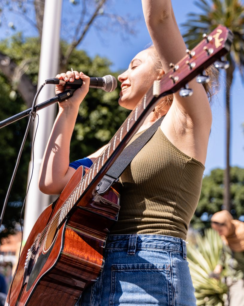 "Los Angeles Youth Climate March organizer Arielle Martinez-Cohen, 17, a senior at New West Charter School in West Los Angeles performs for students and other climate marchers in front of Los Angeles City Hall on Friday, March 15, 2019. Of the march, Martinez-Cohen said, ""It's super exciting to see all these students fighting for the same cause."" When asked what comes next, she offered, ""We want to bring our demands to our city hall legislators. We want to have Los Angeles carbon neutral by 2030. We're on schedule for 2045, but that's not soon enough. The City of Los Angeles has been taking the initiative, and we don't want to spread hate, we want to spread love. But we can't wait till 2045. We have to be 100% carbon neutral by 2030."" (Glenn Zucman/The Corsair)"