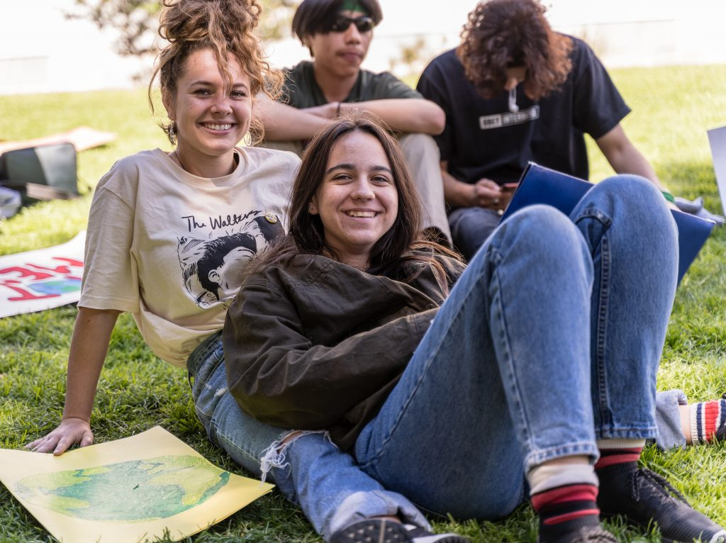 "Celeste Cannon, 16, and Emilia Violich, 15, both from Archer School for Girls in Brentwood, Los Angeles relax on the grass and listen to speakers at the Youth Climate March in front of Los Angeles City Hall on Friday, March 15, 2019. Cannon said they were there because ""We really care about the environment."" Violich said, ""The world is dying and something needs to be done about it."" ""Fridays for the Future"" is organized by 16-year-old Swede Greta Thunberg. The Los Angeles Youth Climate March is organized by 17-year-old Los Angeleño Arielle Martinez-Cohen. (Glenn Zucman/The Corsair)"