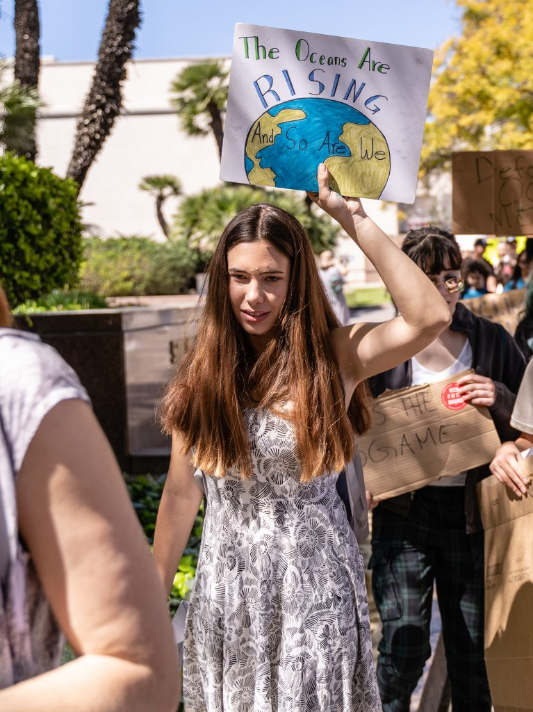 "Phoebe Dickinson, 15, from South Pasadena High School marches toward Los Angeles City Hall in the Youth Climate Strike on Friday, March 15, 2019. Dickinson said, ""I'm here because I want the planet to have a future and I think humans are ruining it."" ""Fridays for the Future"" is organized by 16-year-old Swede Greta Thunberg. The Los Angeles Youth Climate March is organized by 17-year-old Los Angeleño Arielle Martinez-Cohen. (Glenn Zucman/The Corsair)"