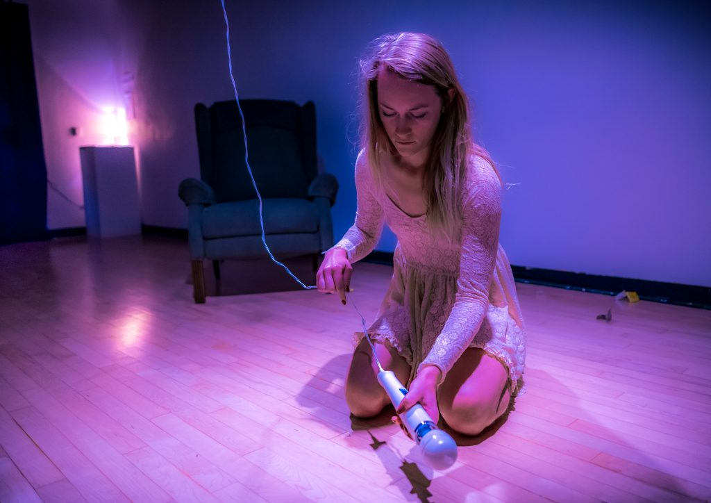 Performance Artwork by Cortnee Brush. Brush is wearing a white, lace dress, and is kneeling on the gallery floor. She holds a vibrator in her hand. The vibrator has a cord that goes up to the gallery ceiling.