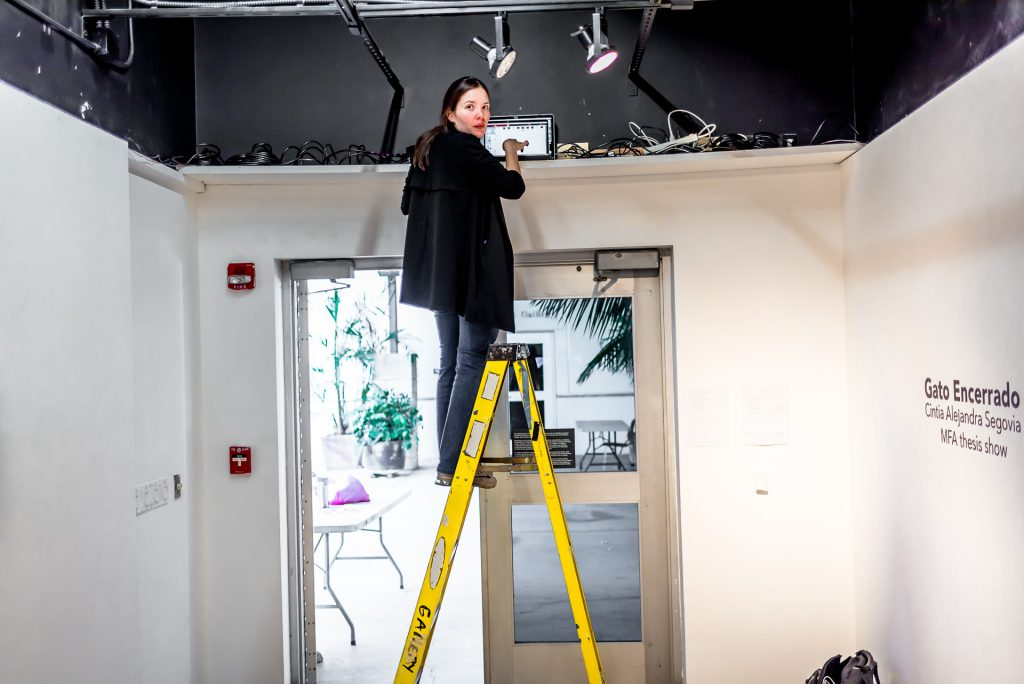Cintia Segovia on a ladder in the LBSU Merlino Gallery adjusting the video program being distributed to the monitors in her gallery installation.