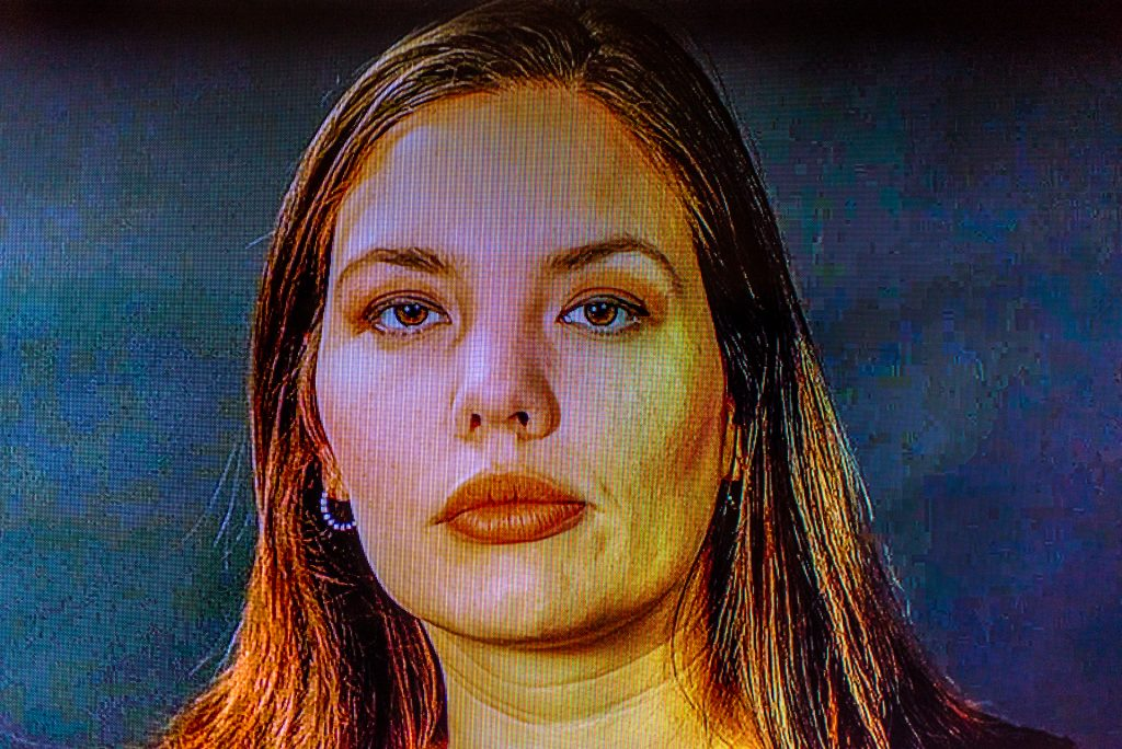 photo of a video screen running a video of Cintia Segovia looking at the camera.
