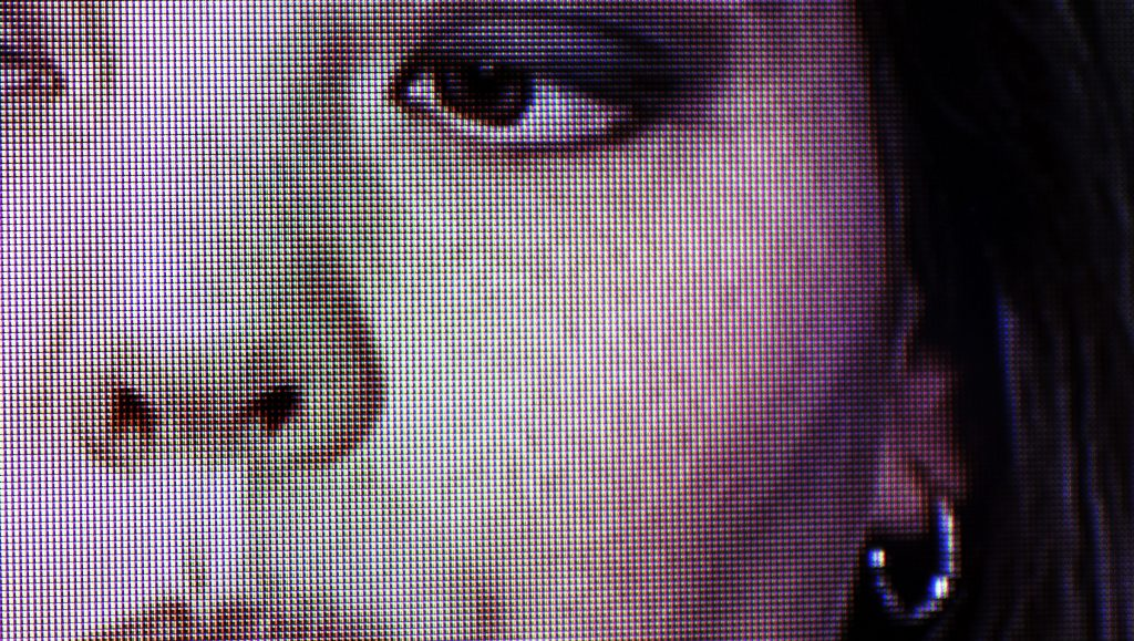 detail view of a video monitor showing the pixels that compose an image of Cintia Segovia's face