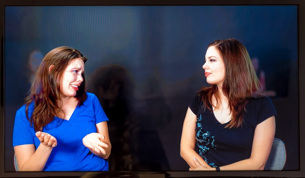 """Screen capture of a video program where 2 """"copies"""" of Cintia Segovia sit side by side and speak with each other"""