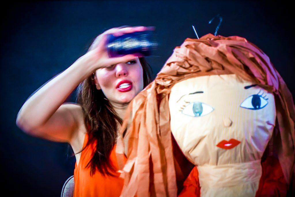video screen capture of Cintia Segovia stuffing a passport into the head of a pinata girl