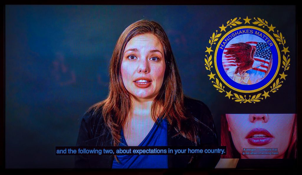 """Video frame capture of Cintia Segovia speaking to the camera with a seal superimposed on the screen. The seal looks like a federal government seal, and carries the words """"handshakes matter"""""""