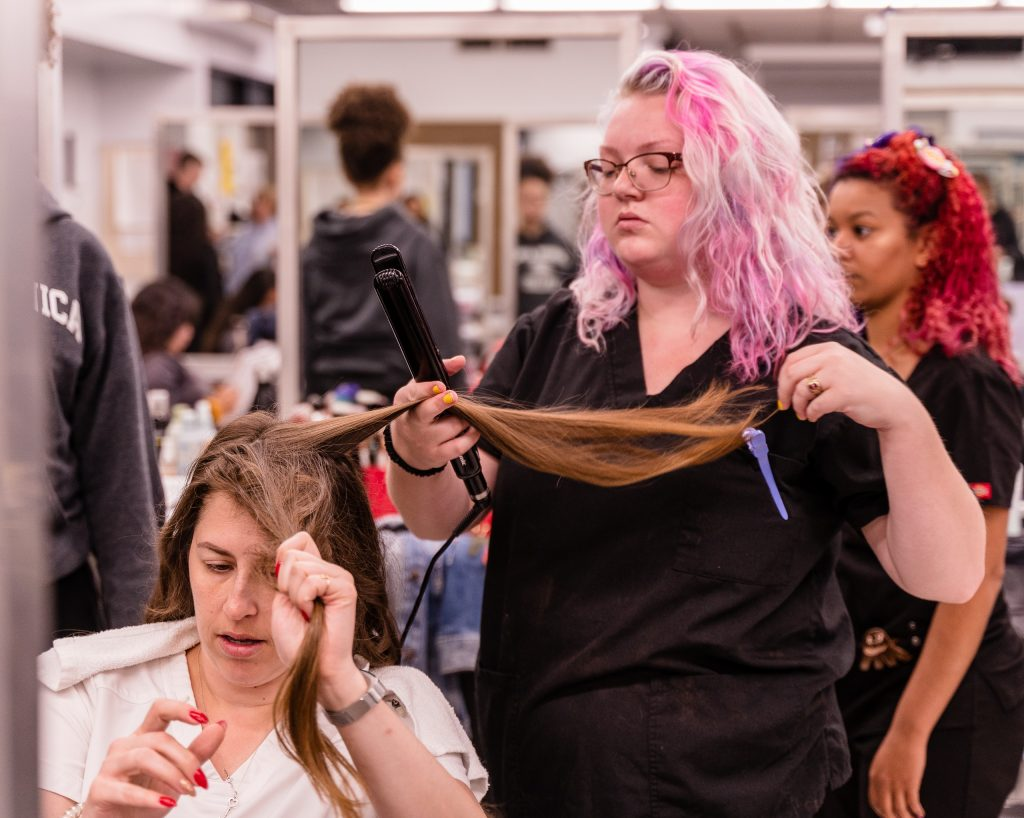 """Alexandra Schulz (right), 22, a 2nd year cosmetology major from Jeffersonville, Indiana curls Kaia Cobb's (left) hair in the SMC Cosmetology salon in the SMC Main Campus Business Building on Thursday, April 18, 2019. Cobb, 34, from Houston, Texas, holds a 2007 BBA in Economics from Baylor University in Waco, Texas. She enrolled in the Esthetician Program at SMC to pursue her """"teenage dream of being a makeup artist in Los Angeles."""" (Glenn Zucman/The Corsair)"""