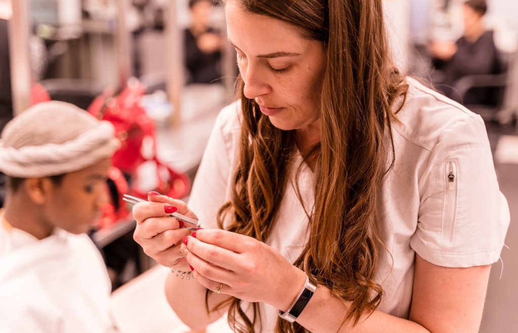 """Kaia Cobb, 34, From Houston, Texas, Applies Glue To A False Eyelash At The SMC Cosmetology Salons In The Business Building On SMC's Main Campus On Thursday, April 18, 2019. Cobb Holds A 2007 BBA In Economics From Baylor University In Waco, Texas. She Enrolled In The Esthetician Program At SMC To Pursue Her """"Teenage Dream Of Being A Makeup Artist In Los Angeles."""" (Glenn Zucman/The Corsair)"""