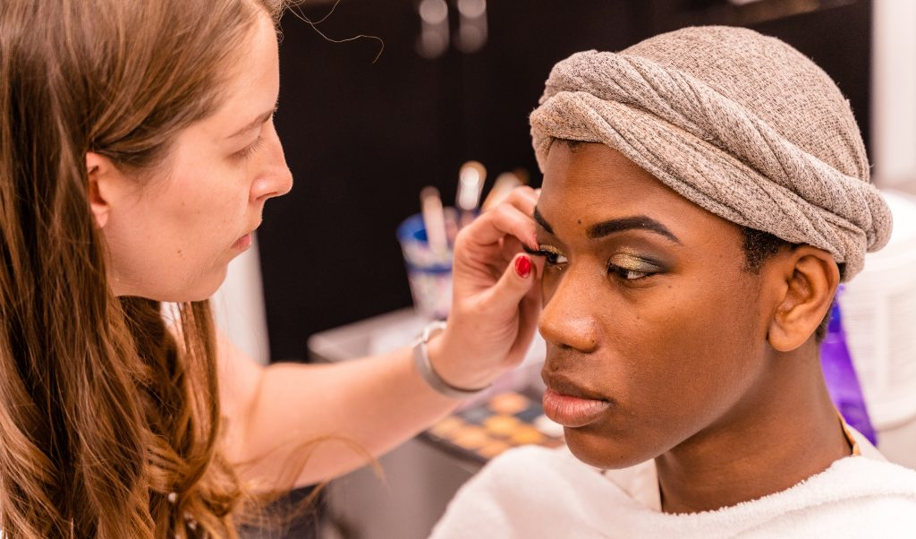 "Kaia Cobb, 34, From Houston, Texas, Applies A False Eyelash To Skye Johnson, 18, A Brooklyn, NY Born, And Raleigh, NC Raised, Student In The SMC Esthetician Program At The SMC Cosmetology Salons In The Business Building On SMC's Main Campus On Thursday, April 18, 2019. In Addition To The Esthetician Program, Johnson Is Also Taking His Nursing Prerequisites At SMC With The Goal Of Becoming A Medical Aesthetician. Medical Aestheticians Provide Skin Care In Medical Settings And Can Assist With Injectables Like Botox. Cobb Holds A 2007 BBA In Economics From Baylor University In Waco, Texas. She Enrolled In The Esthetician Program At SMC To Pursue Her ""Teenage Dream Of Being A Makeup Artist In Los Angeles."" (Glenn Zucman/The Corsair)"