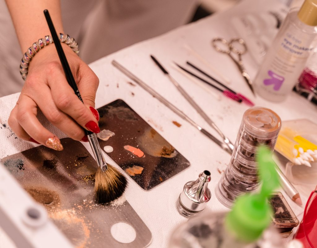 """SMC Esthetician Program Student Kaia Cobb, 34, From Houston, Texas, Applies Powder To A Brush In The SMC Cosmetology Salons In The Business Building On SMC's Main Campus On Thursday, April 18, 2019. Of Her Vast Collection Of Makeup Supplies, Cobb Says, """"I Have To Know Who My Client Is Before I Take All My Products Out."""" (Glenn Zucman/The Corsair)"""