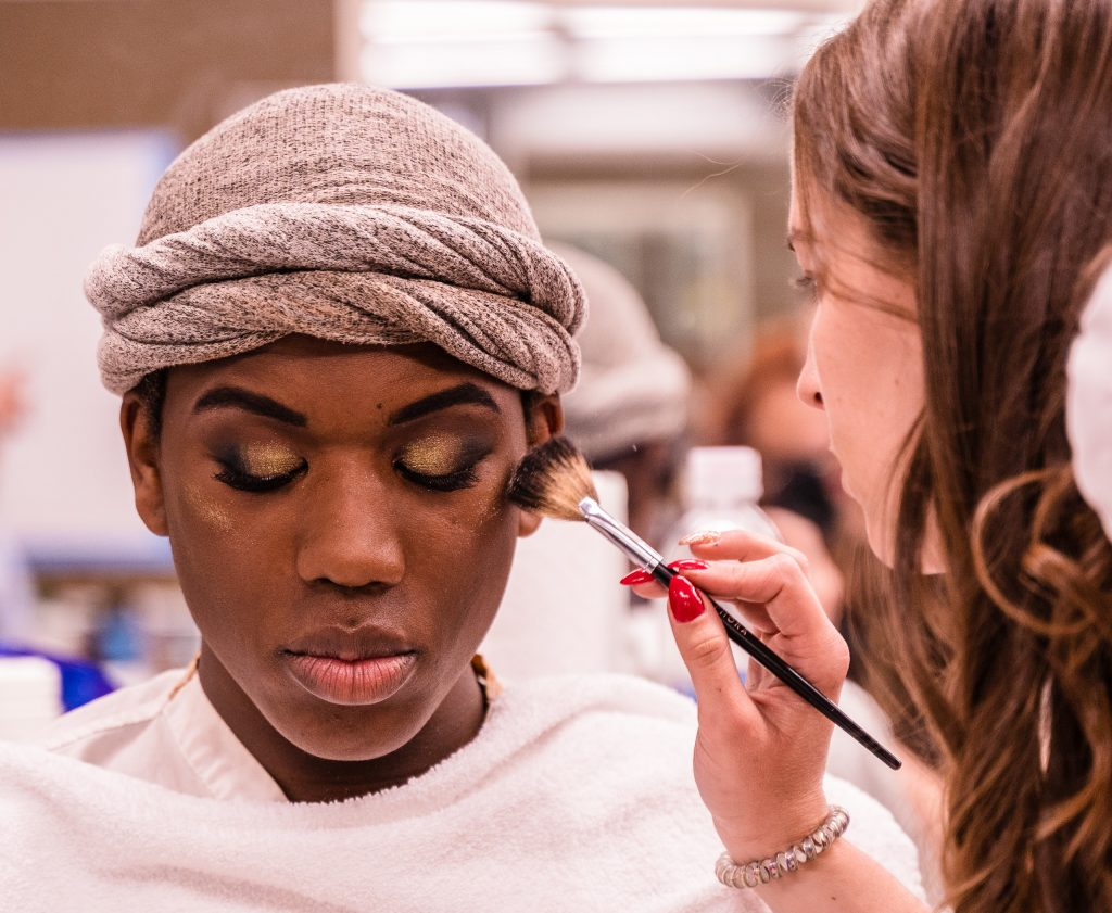 """Kaia Cobb, 34, From Houston, Texas, Applies Makeup To Skye Johnson, 18, A Brooklyn, NY Born, And Raleigh, NC Raised, Student In The SMC Esthetician Program At The SMC Cosmetology Salons In The Business Building On SMC's Main Campus On Thursday, April 18, 2019. In Addition To The Esthetician Program, Johnson Is Also Taking His Nursing Prerequisites At SMC With The Goal Of Becoming A Medical Aesthetician. Medical Aestheticians Provide Skin Care In Medical Settings And Can Assist With Injectables Like Botox. Cobb Holds A 2007 BBA In Economics From Baylor University In Waco, Texas. She Enrolled In The Esthetician Program At SMC To Pursue Her """"Teenage Dream Of Being A Makeup Artist In Los Angeles."""" (Glenn Zucman/The Corsair)"""