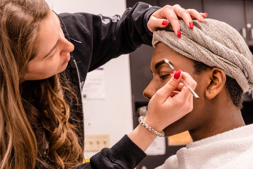 "Kaia Cobb, 34, From Houston, Texas, Applies Makeup To Skye Johnson, 18, A Brooklyn, NY Born, And Raleigh, NC Raised, Student In The SMC Esthetician Program At The SMC Cosmetology Salons In The Business Building On SMC's Main Campus On Thursday, April 18, 2019. In Addition To The Esthetician Program, Johnson Is Also Taking His Nursing Prerequisites At SMC With The Goal Of Becoming A Medical Aesthetician. Medical Aestheticians Provide Skin Care In Medical Settings And Can Assist With Injectables Like Botox. Cobb Holds A 2007 BBA In Economics From Baylor University In Waco, Texas. She Enrolled In The Esthetician Program At SMC To Pursue Her ""Teenage Dream Of Being A Makeup Artist In Los Angeles."" (Glenn Zucman/The Corsair)"