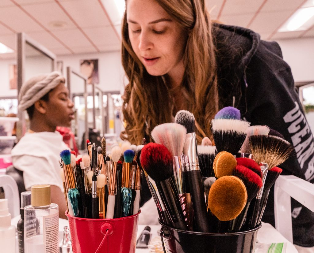 "Kaia Cobb, 34, From Houston, Texas, Selects One Of Her Brushes To Apply Makeup To Skye Johnson, 18, A Brooklyn, NY Born, And Raleigh, NC Raised, Student In The SMC Esthetician Program At The SMC Cosmetology Salons In The Business Building On SMC's Main Campus On Thursday, April 18, 2019. Of Her Vast Collection Of Makeup Supplies, Cobb Says, ""I Have To Know Who My Client Is Before I Take All My Products Out."" (Glenn Zucman/The Corsair)"