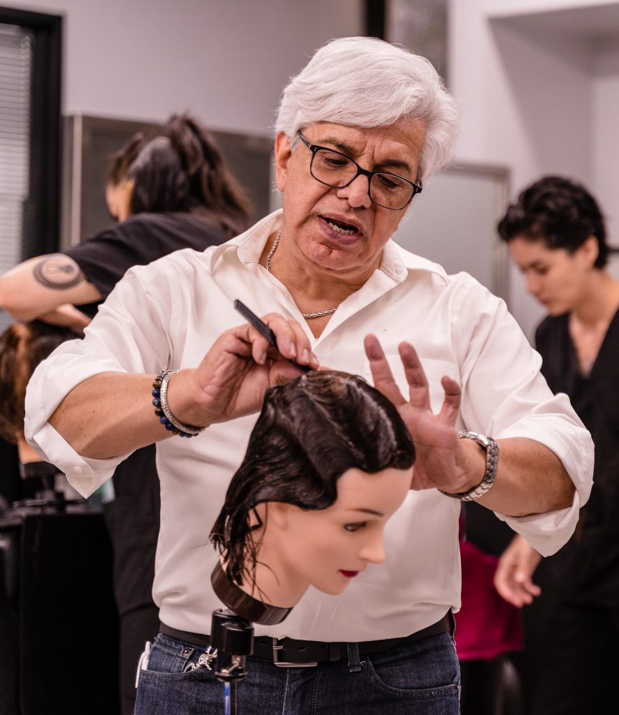 SMC Cosmetology Faculty Member Felipe Felix Demonstrating Hair Styling Techniques In The SMC Cosmetology Salon In The Business Building On Main Campus On Thursday, April 18, 2019. Felix Has Taught In The SMC Cosmetology Department Since 1989. (Glenn Zucman/The Corsair)