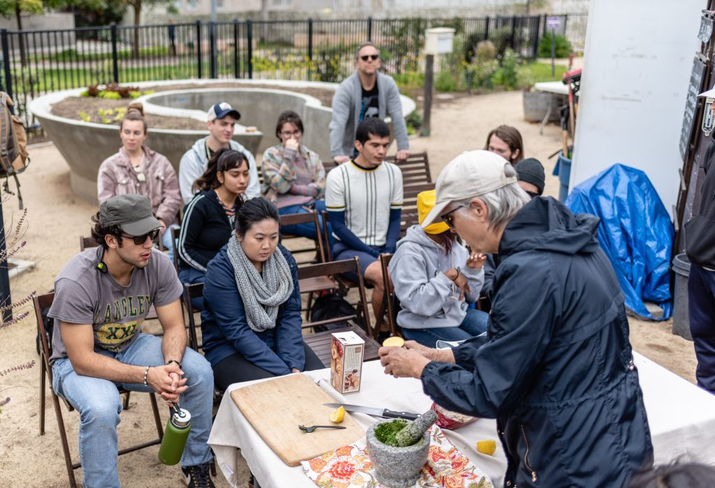 SMC Organic Learning Garden Leader Dana Morgan, A Master Gardener From University Of California Cooperative Extension, (UCCE) And A Retired SMC English Professor, Teaches Members Of Club Grow How To Make Fava Pesto At Their Weekly Meeting In The Organic Learning Garden (OLG) On SMC's Main Campus On Tuesday, March 5, 2019. Club Grow Meets In The OLG Every Tuesday. (Glenn Zucman/The Corsair)