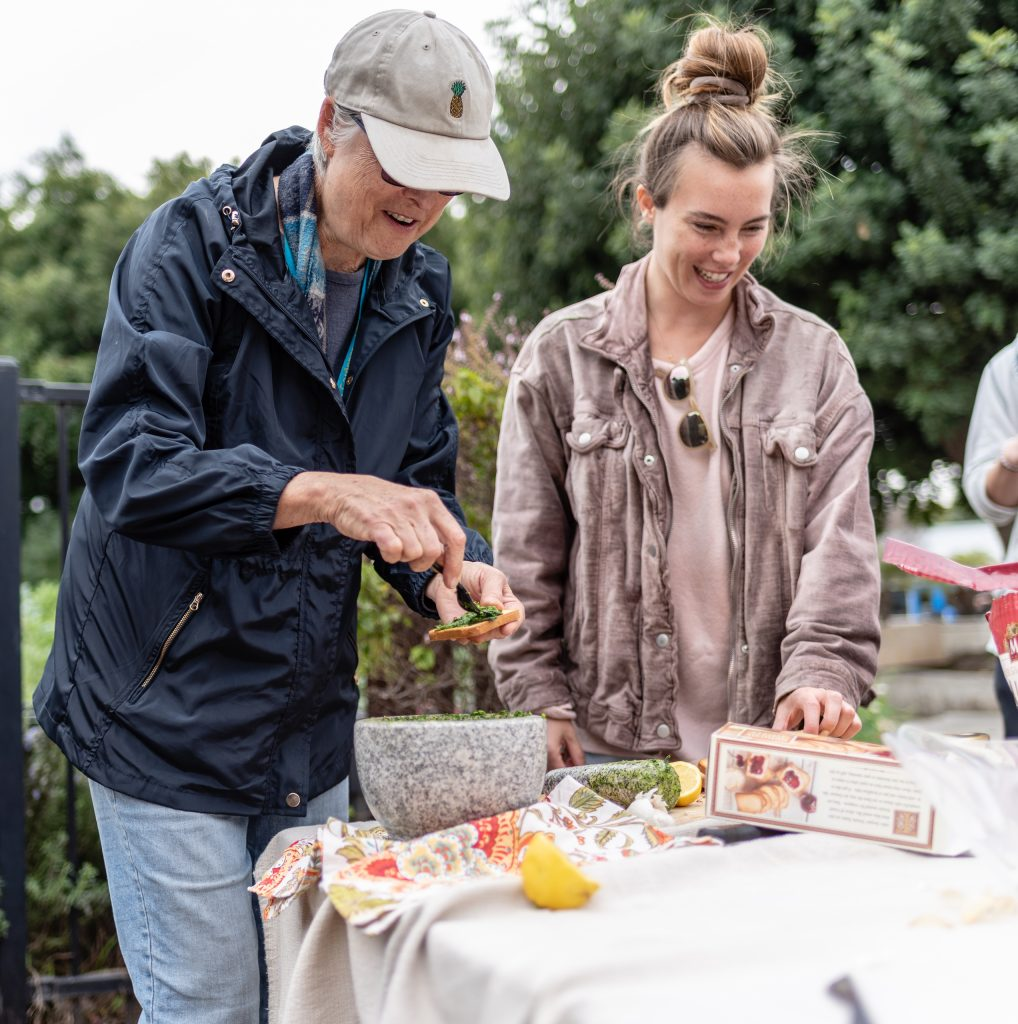 SMC Organic Learning Garden Leader Dana Morgan, A Master Gardener From University Of California Cooperative Extension, (UCCE) And A Retired SMC English Professor, And Madlyn Spence, A 27 Year-Old Conservation Biology Major From Chicago Pass Out Tasting Samples Of Freshly Made Fava Pesto Featuring Ingredients Grown In The SMC Organic Learning Garden (OLG) On Tuesday, March 5, 2019. Spence Has Been Participating At The OLG Since 2010 And Says That The Garden Has Really Influenced Her Major. Attending SMC On And Off, Spence Noted That The Friends She Started SMC With Are All Gone Now And That She Too Has Started To Apply To A Few University Of California Campuses To Finish Her Education. (Glenn Zucman/The Corsair)