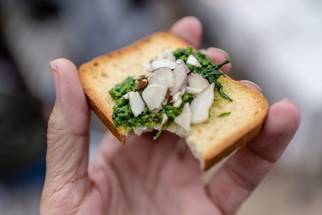 "Fresh Fava Pesto With Sliced Almonds On A Cracker. SMC Students Picked Fava Leaves Grown In The Organic Learning Garden On SMC's Main Campus On Tuesday, March 5, 2019, And Then Ground The Leaves In A Mortar And Pestle. SMC Organic Learning Garden Leader Dana Morgan, A Master Gardener From University Of California Cooperative Extension, (UCCE) And A Retired SMC English Professor Commented That ""Every Household Should Have A Mortar And Pestle. The Cuisinart Just Turns It To Mush."""