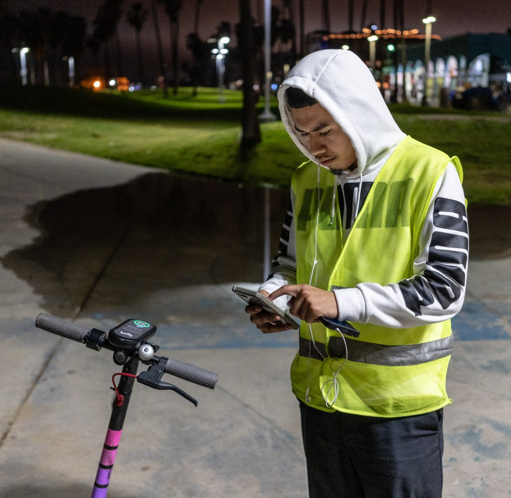 Lyft Employee Michael Jones, 19, From Los Angeles, Calif., Looking Around The Venice Beach Boardwalk For An EScooter In Need Of Charging On Thursday, Feb. 28, 2019. His Mobile App Led Him To This EScooter, But This One Turned Out To Be In Working Order, So Jones Had To Hunt Around For Several Minutes Looking For The EScooter That Needed Charging. Once Found, Jones Will Take The EScooter Back To The Lyft Warehouse Near The SMC Main Campus. At The Lyft Warehouse About 2,000 EScooters Are Charged And Repaired For Use Around Los Angeles. Jones Has Been Working For Lyft Since They Started EScooters In This Area In September 2018. (Glenn Zucman/The Corsair)