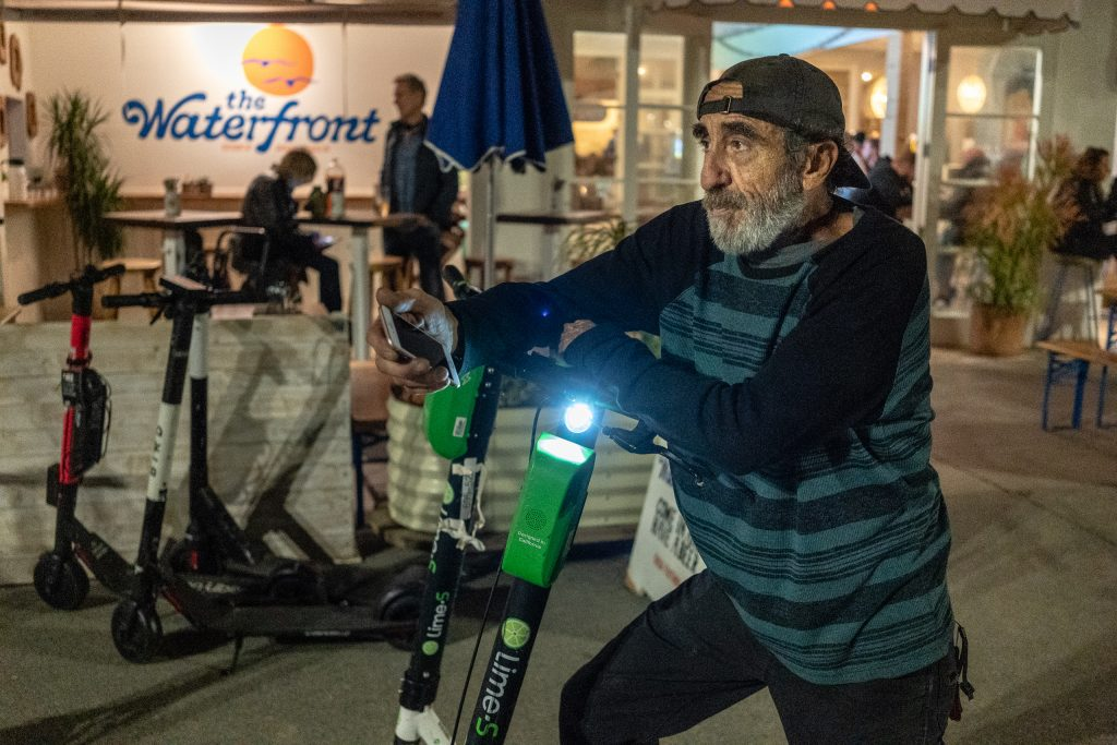"""Scooter Keeper"" Alex, 61, From Santa Monica, Calif., With Lime EScooters He Has Collected In The Venice Beach Area On The Evening Of Thursday, Feb. 28, 2019. Alex Will Take The EScooters Home With Him To Charge Them And Then Put Them Back Out. Lime Pays Him $5 Per Scooter. Alex Stopped Collecting Bird EScooters When They Dropped The Pay From $5/Scooter To $3/Scooter. Alex Knows That Some Companies Like Uber And Lyft Have Full-Time Jobs Collecting EScooters, But He Doesn't Want That Kind Of Constraint At His Age. He Enjoys The Freedom Of Collecting EScooters When He Chooses. (Glenn Zucman/The Corsair)"