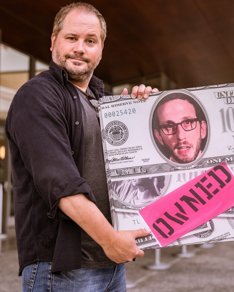 "Lawyer And Journalist Chris Legras Of Santa Monica Holds A Sign Questioning The Motives Of California State Senator Scott Weiner's (SD11 – San Francisco) SB 50 Which Proposes New Approaches To California's Housing Issues, Outside The The Broad Stage At The SMC Performing Arts Center On Thursday, May 9, 2019. Legras Said, ""I Worry About SB-50, It's A Poorly Planned, Rushed Solution To A Problem We All Know Exists. It's Going To Effect The Poor And Marginalized The Most."" The SMC Public Policy Institute Is Presenting Its 8th Annual Spring Symposium, ""There Goes The Neighborhood, Part II: How Might Policy Approaches Prevent Displacement In Neighborhoods Affected By Gentrification?"" From May 4-9. Tonight's Final Event In The Series Is ""Where Goes The Road To Solving California's Housing Crisis? A Keynote Discussion With Legislative Leaders."" The Panel Includes California State Legislators Senator Ben Allen (SD26 – Santa Monica) And Senator Scott Weiner (SD11 – San Francisco), Author Of SB 50 Which Proposes Bold Approaches To California's Housing Issues, And Santa Monica Mayor Gleam Davis, A Former Co-Chair Of Santa Monicans For Renters' Rights And Leading Advocate For Santa Monica's Innovative Policy Solutions And Funding For Affordable Housing."" (Glenn Zucman/The Corsair)"