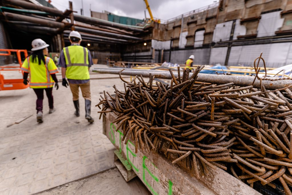 Metro Regional Connector Senior Safety Manager Michelle Jones And Corsair Staff Writer Michael Fanelli Walk Past A Large Bin Of Rebar In The Middle Of The Future Little Tokyo/Arts District Station On Wednesday, April 3, 2019. When Completed In 2022 The Regional Connector Will Add New Stations At Little Tokyo/Arts District, Historic Broadway, And Grand Avenue Arts/Bunker Hill. The Regional Connector Will Simplify East-West And North-South Travel In Los Angeles. A Trip From East Los Angeles College To Santa Monica College Which Currently Requires 2 Transfers And 3 Trains, Will Require Only One Train When This New Segment Opens In 2022. (Glenn Zucman/The Corsair)