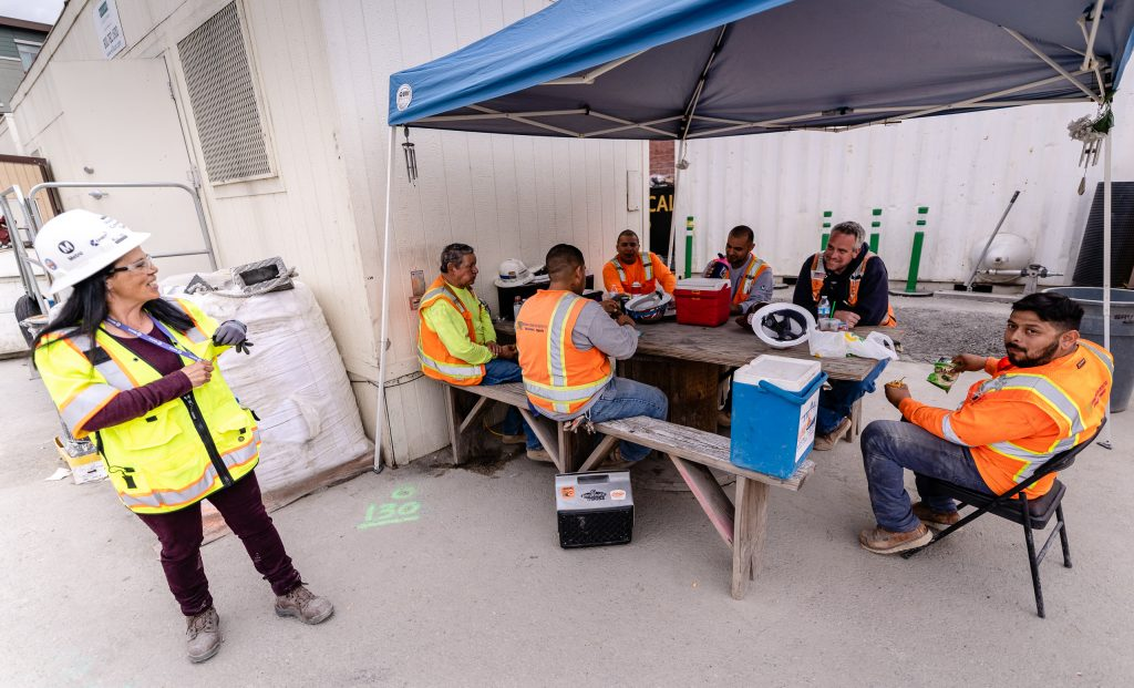 Metro Regional Connector Senior Safety Manager Michelle Jones Talks With Regional Connector Construction Crew Members As They Eat Lunch Just Outside The Little Tokyo/Arts District Construction Site On Wednesday, April 3, 2019. When Completed In 2022 The Regional Connector Will Add New Stations At Little Tokyo/Arts District, Historic Broadway, And Grand Avenue Arts/Bunker Hill. The Regional Connector Will Simplify East-West And North-South Travel In Los Angeles. A Trip From East Los Angeles College To Santa Monica College Which Currently Requires 2 Transfers And 3 Trains, Will Require Only One Train When This New Segment Opens In 2022. (Glenn Zucman/The Corsair)